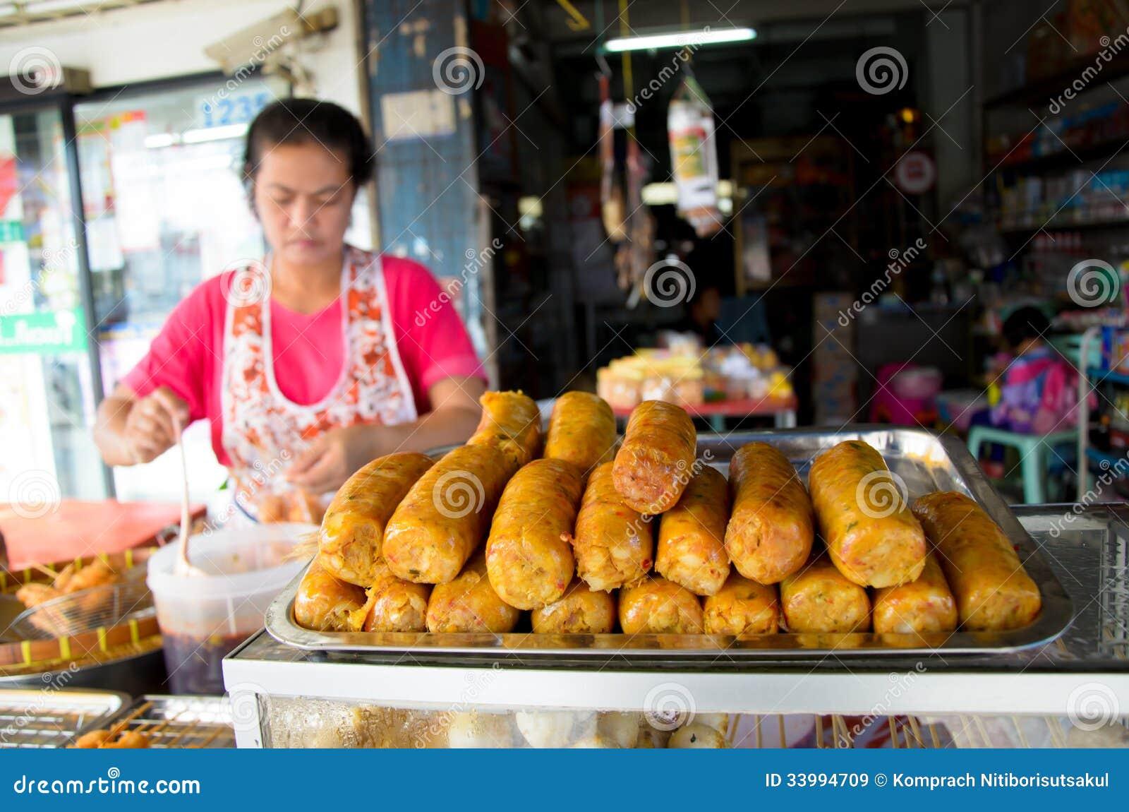 Femme du marché vendant des saucisses.