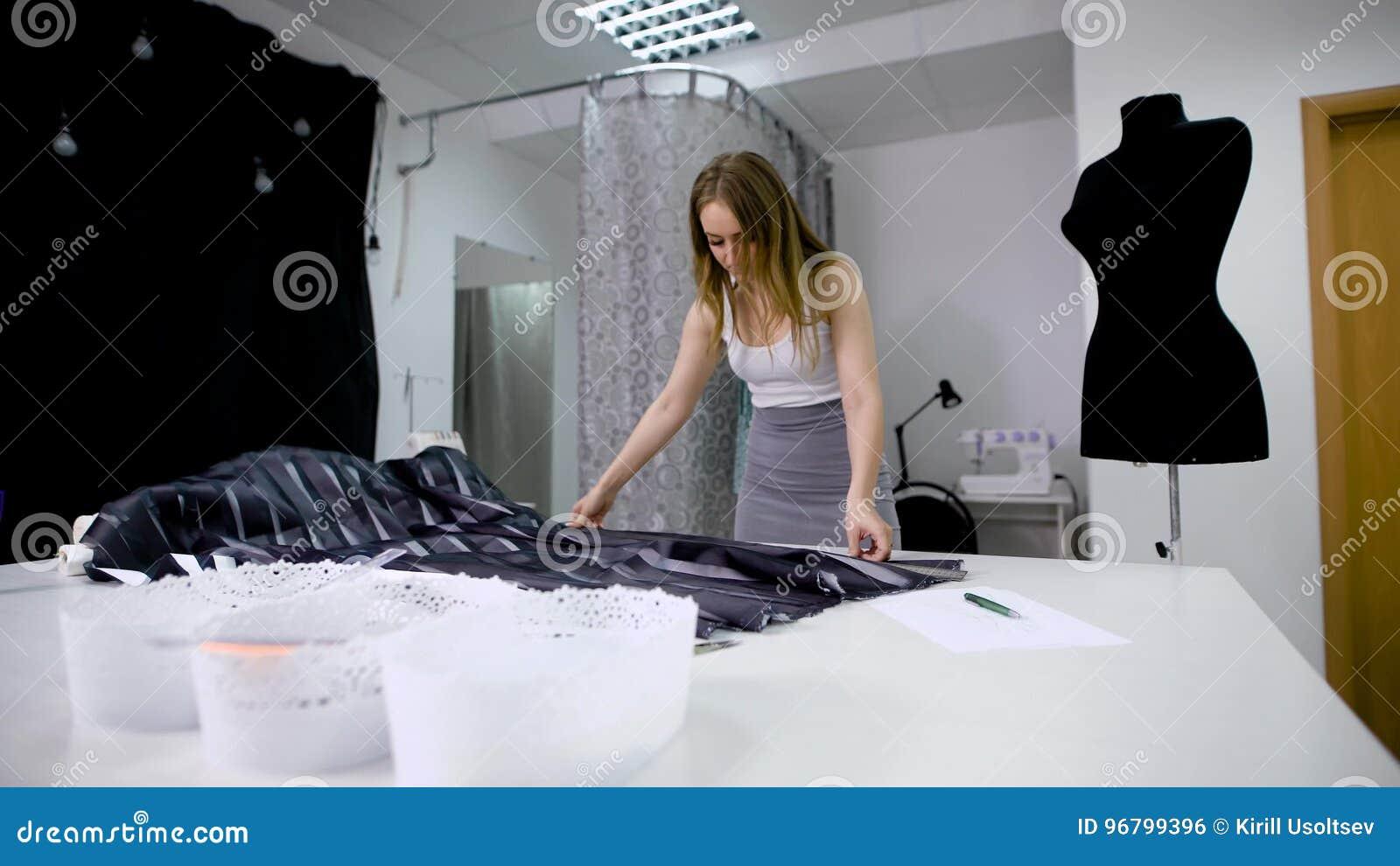 f98c187def8dec Femme en matériel de coupe de boutique de tailleur pour créer de nouveaux  vêtements.