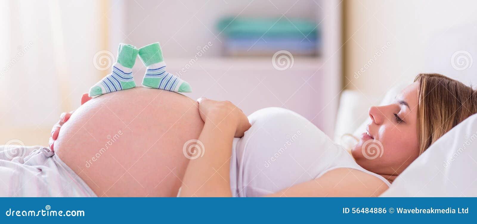 Femme enceinte avec des chaussures de bébé au-dessus de bosse