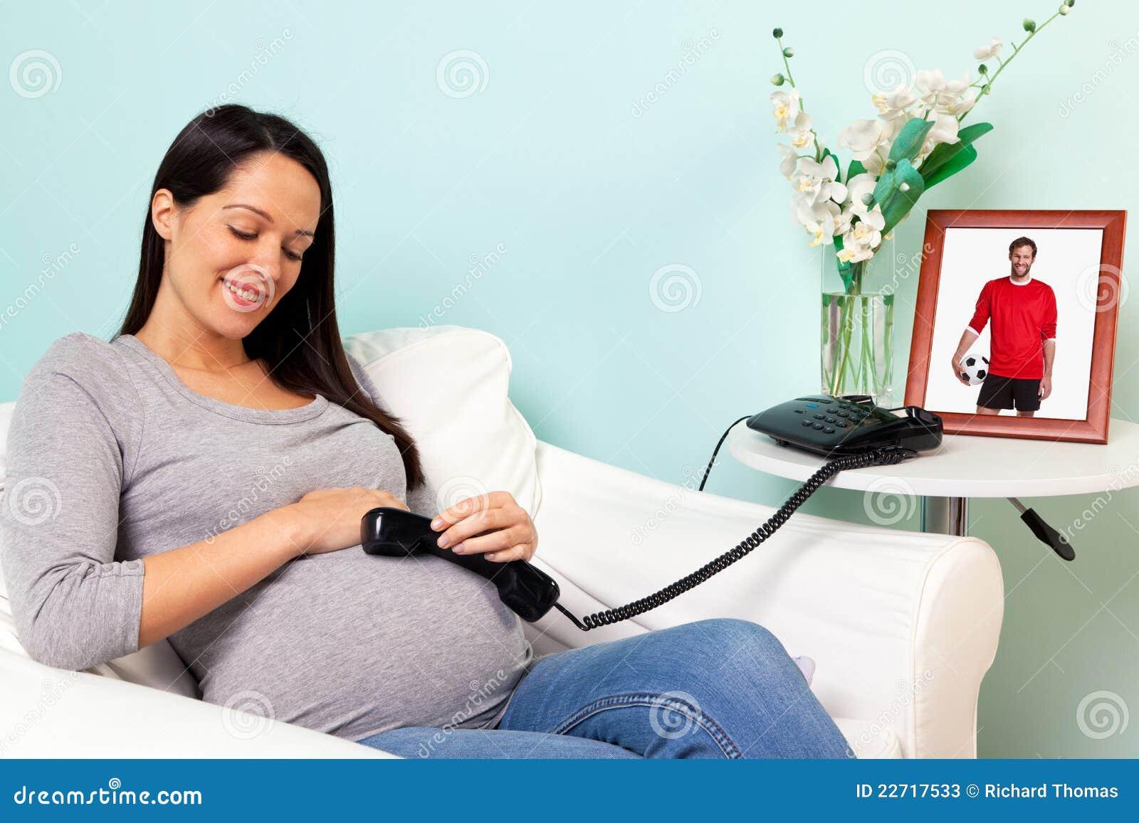 Femme enceinte avec le téléphone parlant au papa