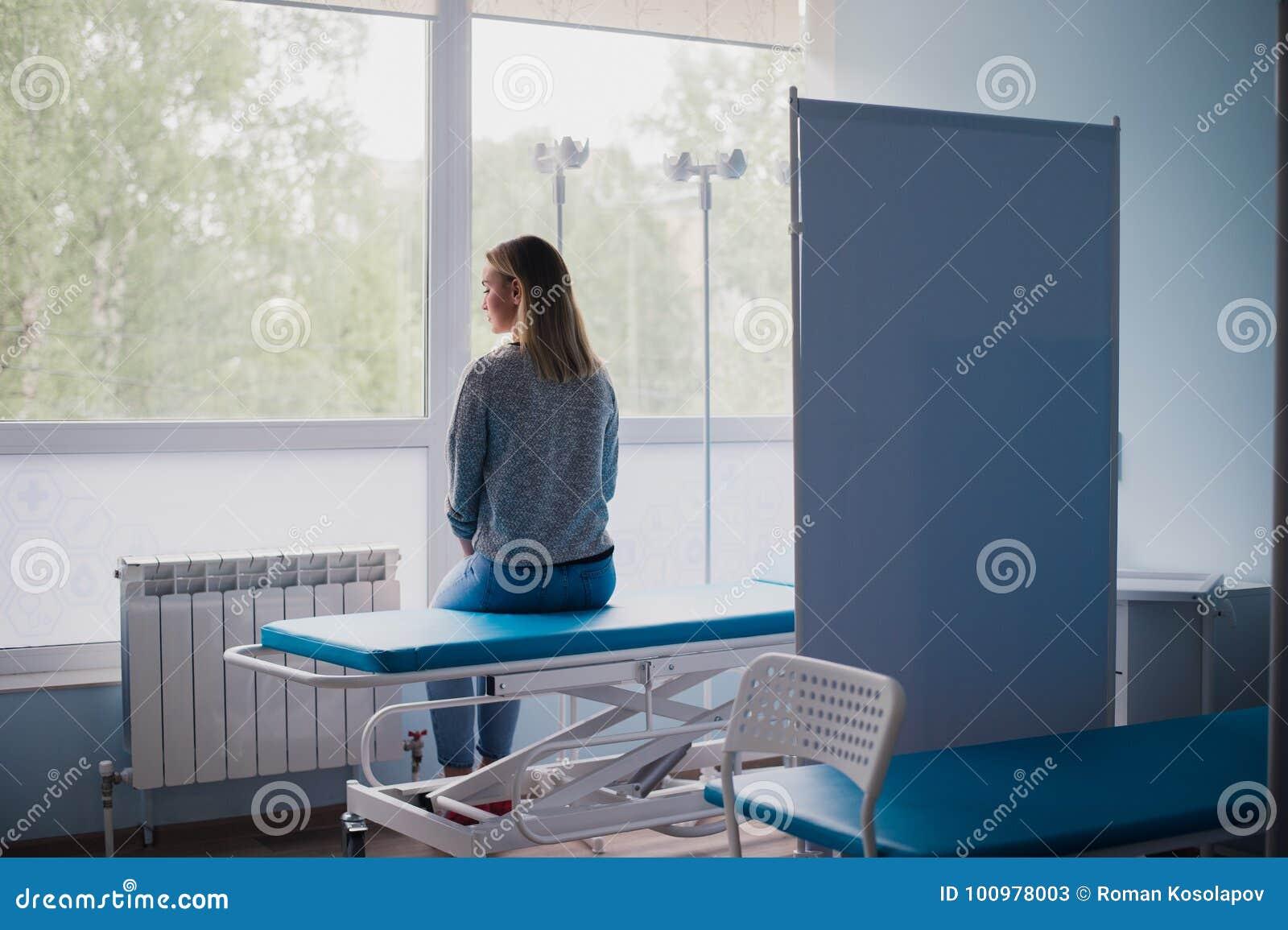 Femme enceinte de jeunes s asseyant sur le lit dans la salle confortable, docteur de attente pensivement