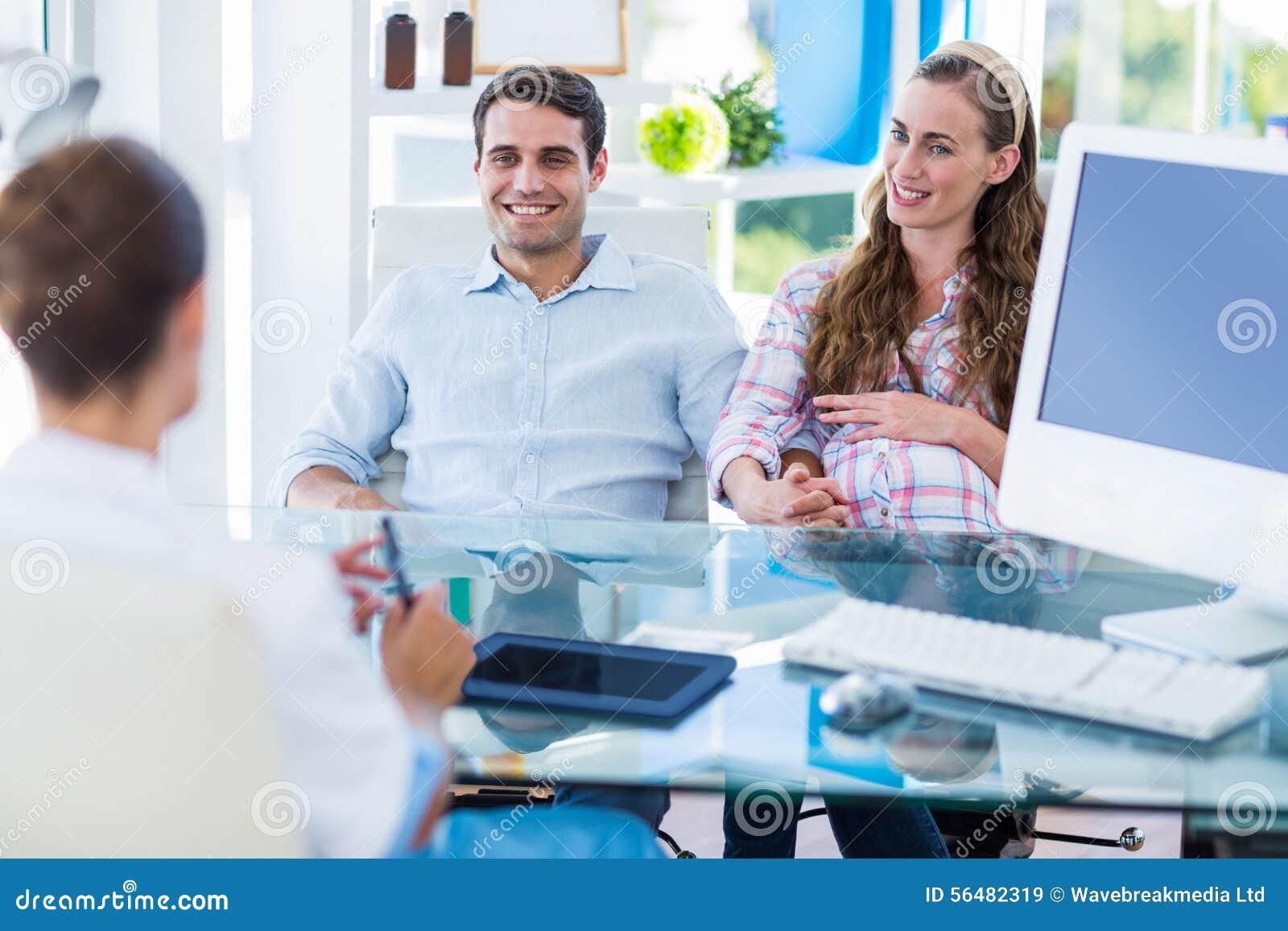Femme enceinte et son mari discutant avec le docteur