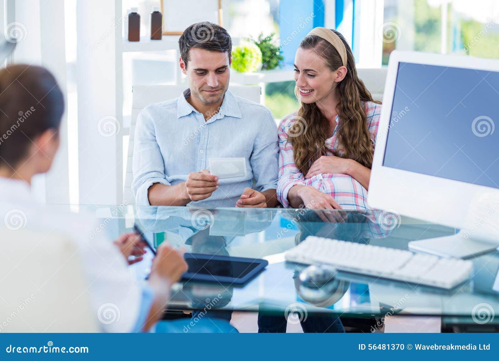 Femme enceinte et son mari regardant la photo de leur futur bébé