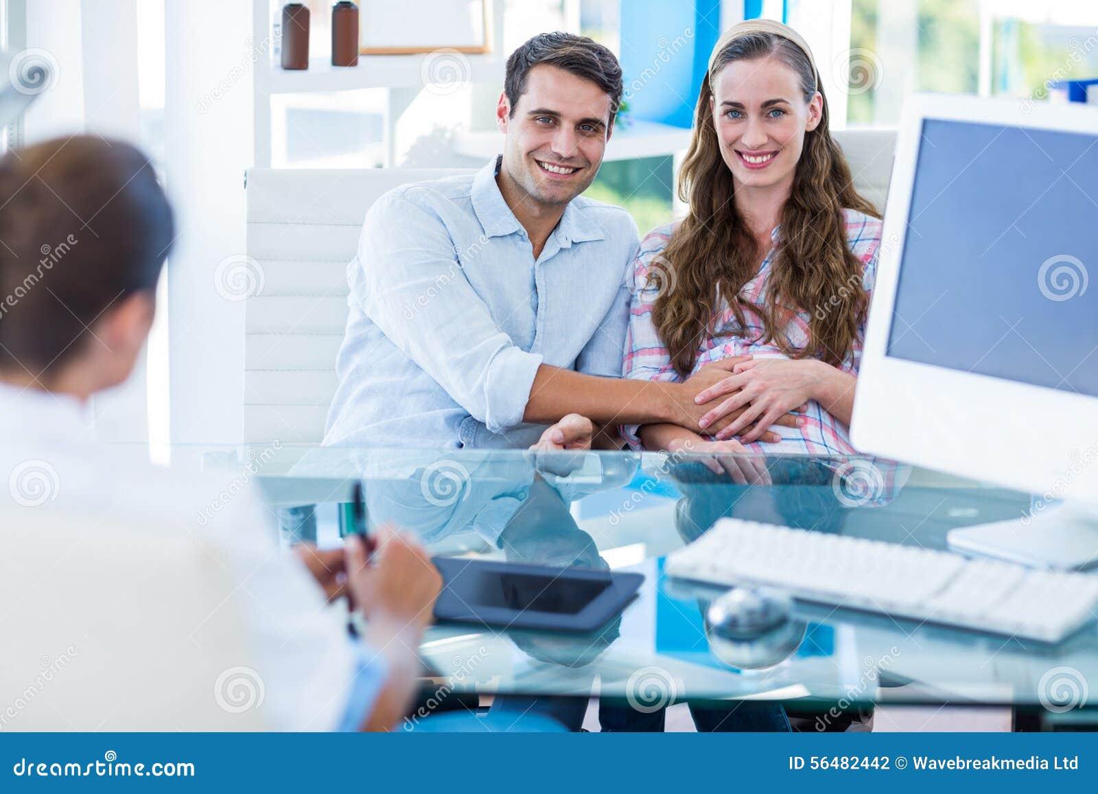 Femme enceinte et son mari souriant à l appareil-photo