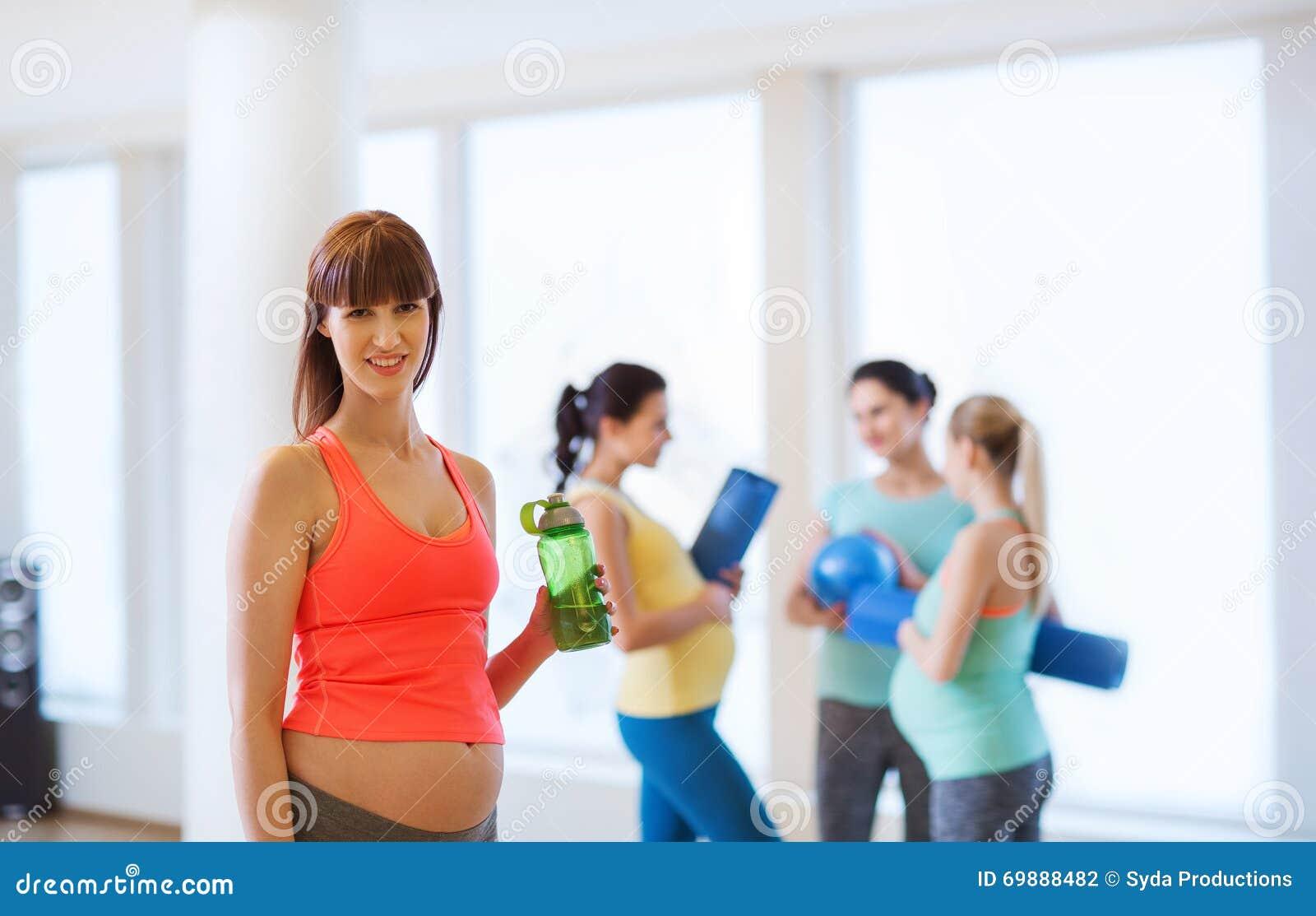 femme enceinte heureuse avec la bouteille d 39 eau dans le gymnase photo stock image du. Black Bedroom Furniture Sets. Home Design Ideas