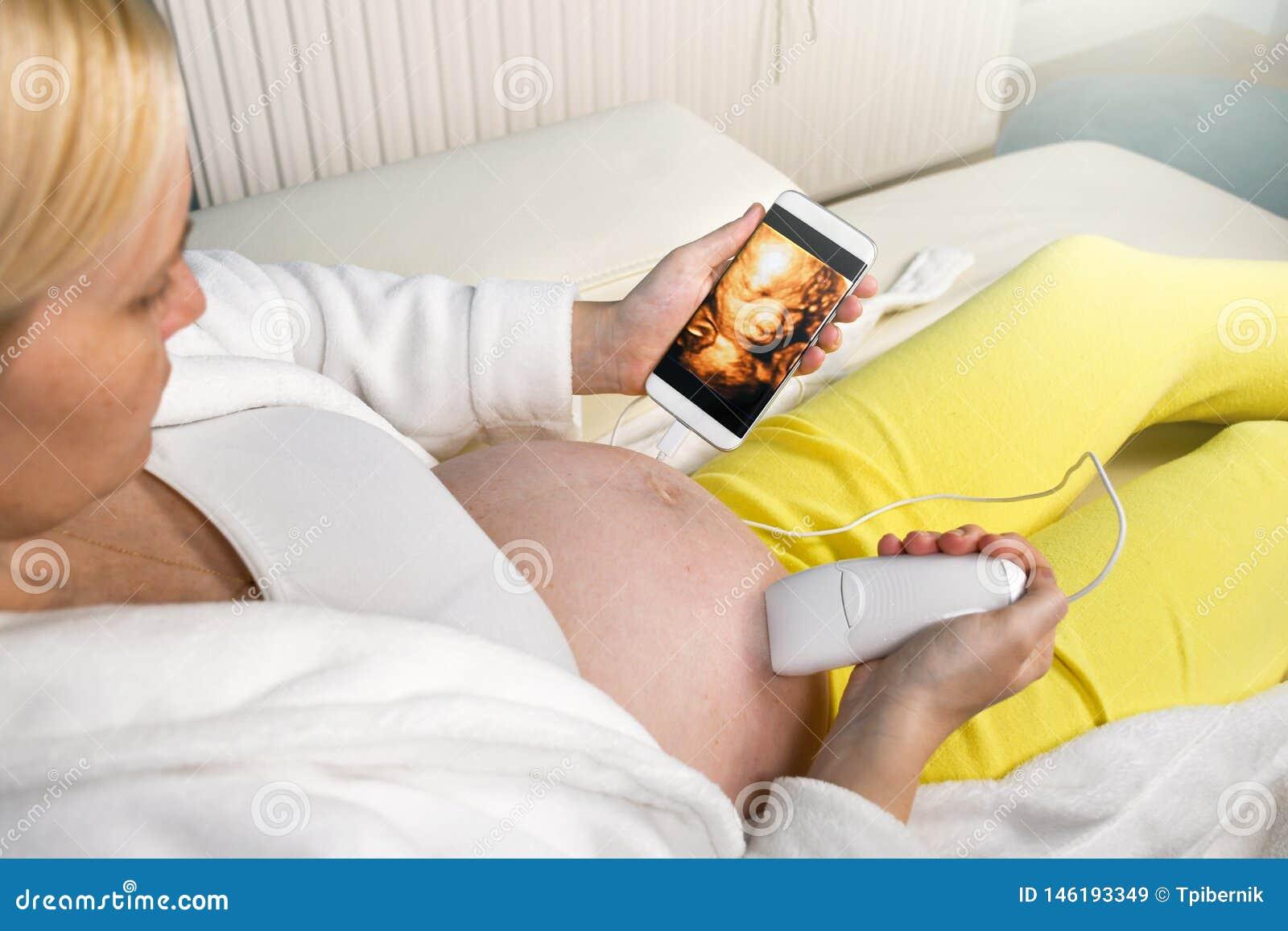 Femme enceinte moderne s asseyant sur un divan blanc ? la maison d?tendant et faisant seule l ultrason 3D num?rique