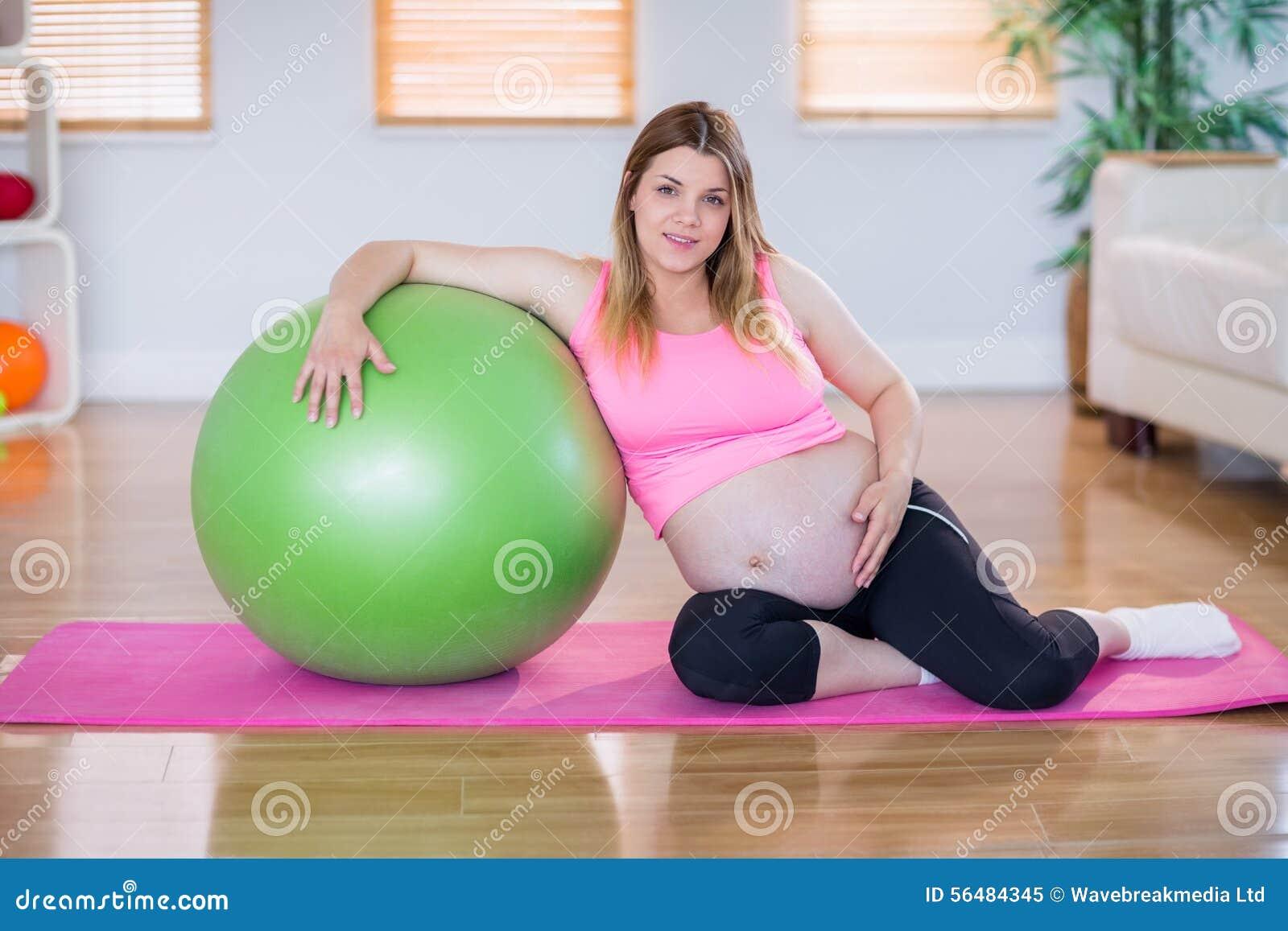 Femme enceinte regardant l appareil-photo avec la boule d exercice