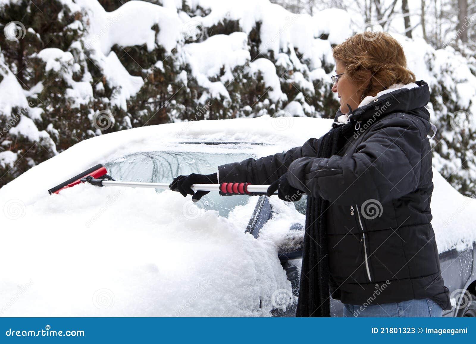 Femme enlevant la neige de son véhicule