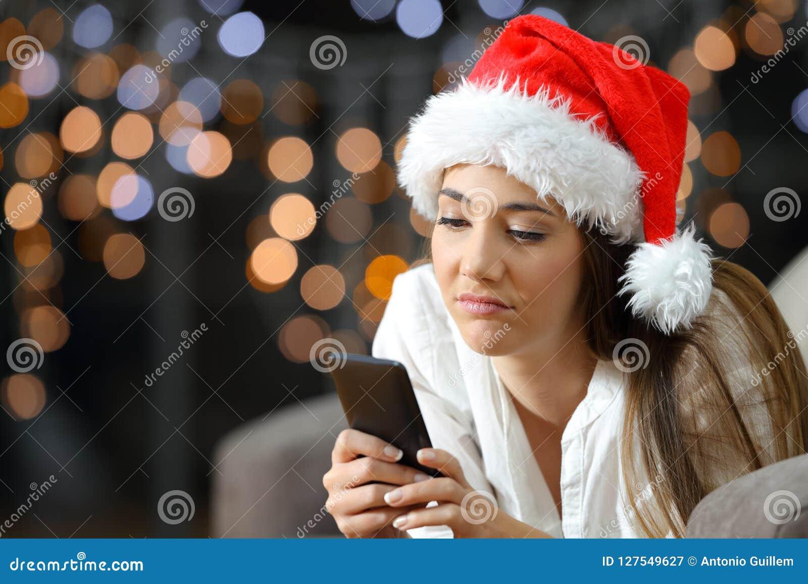 Femme ennuyée ou triste vérifiant le téléphone dans Noël