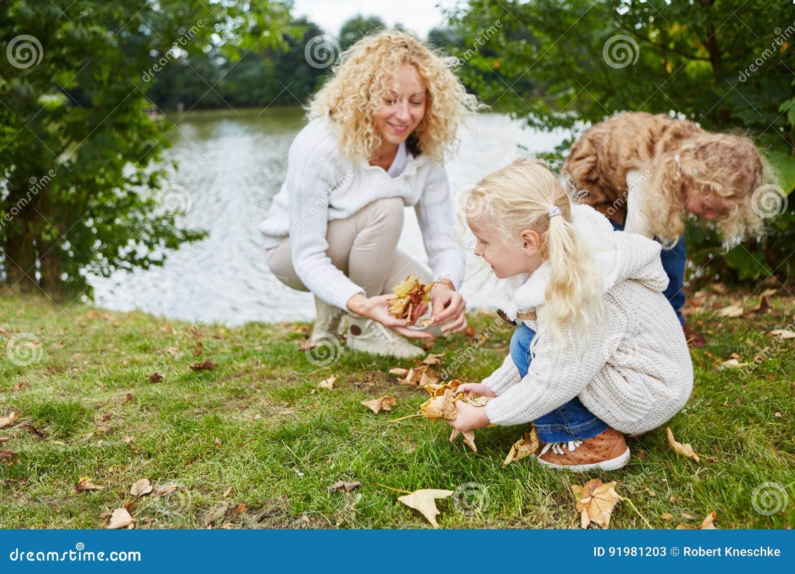 Femme et enfants rassemblant des feuilles