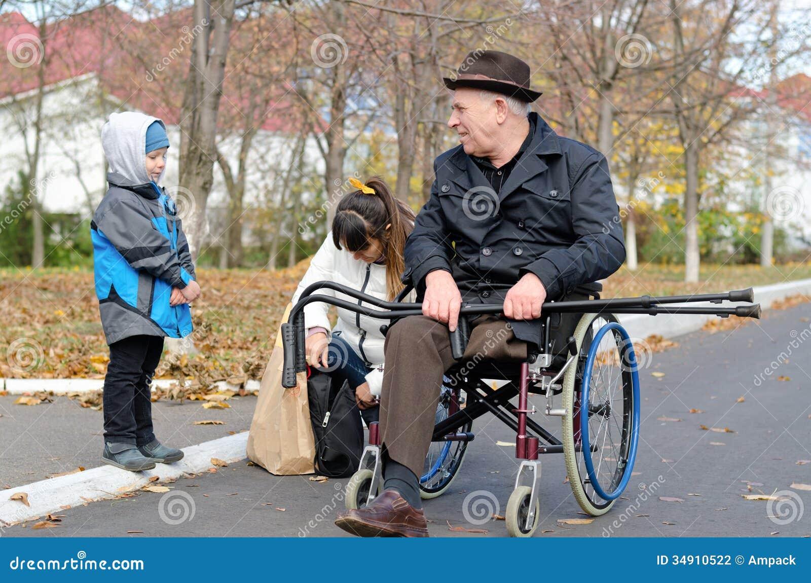 Femme et son fils aidant un vieil homme handicapé
