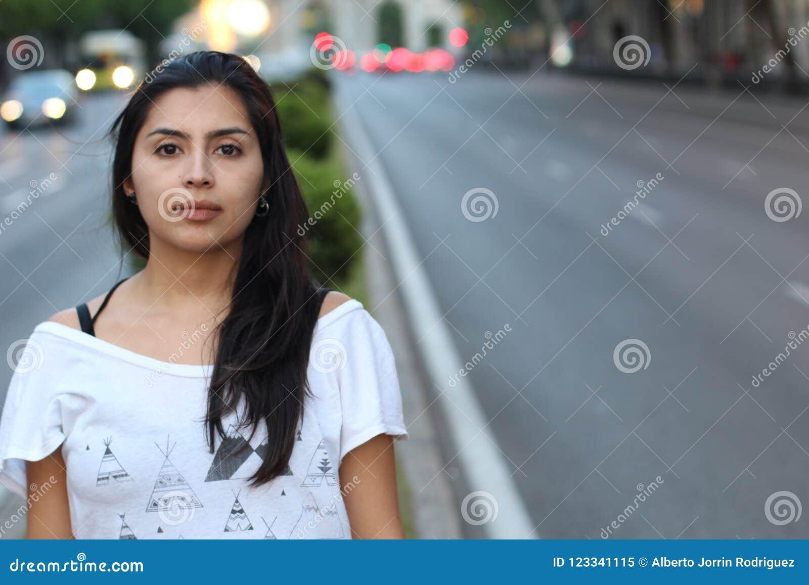 Femme ethnique rêvassant sur la rue
