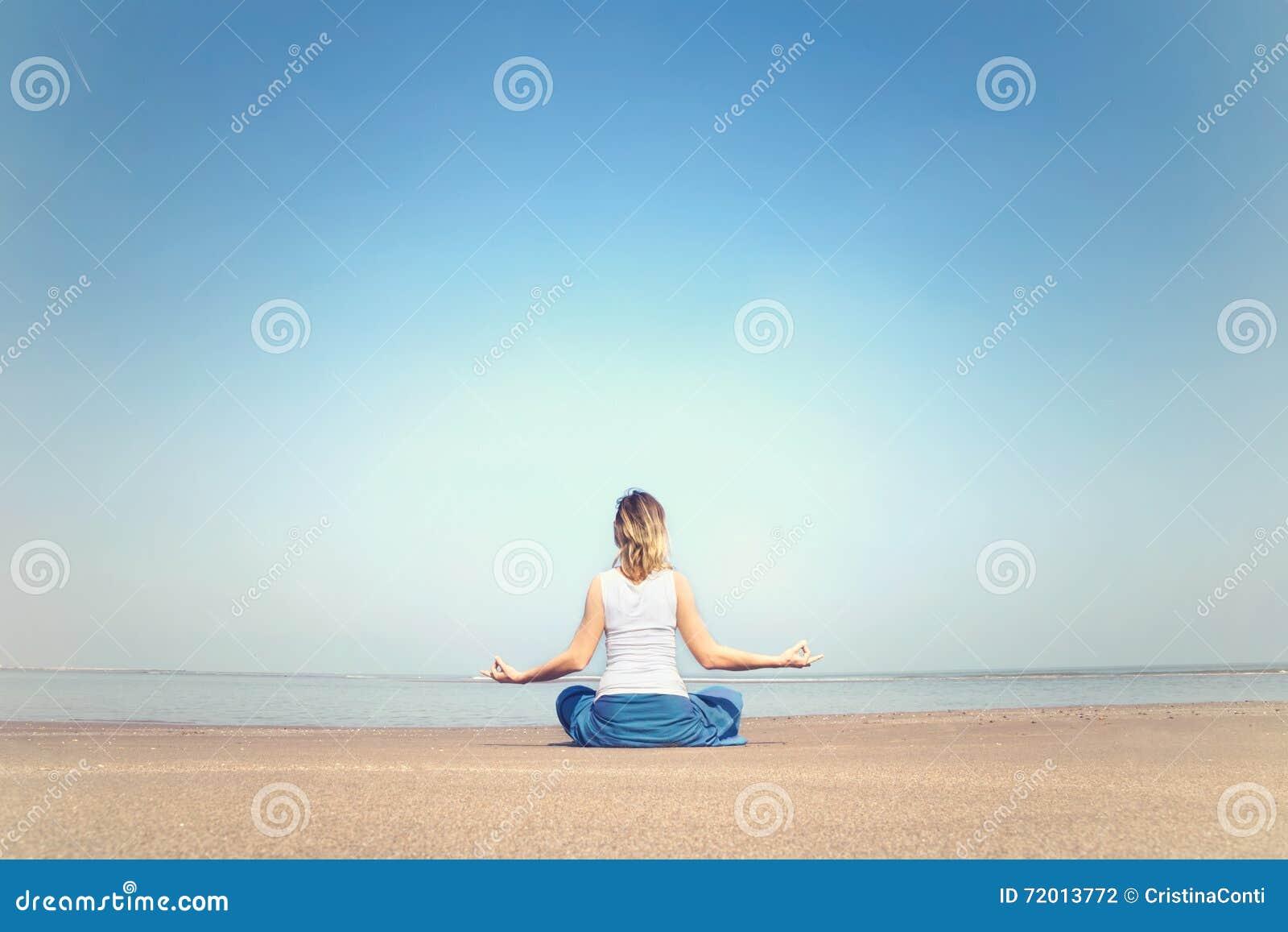 Femme exécutant des exercices de relaxation et de méditation à la mer