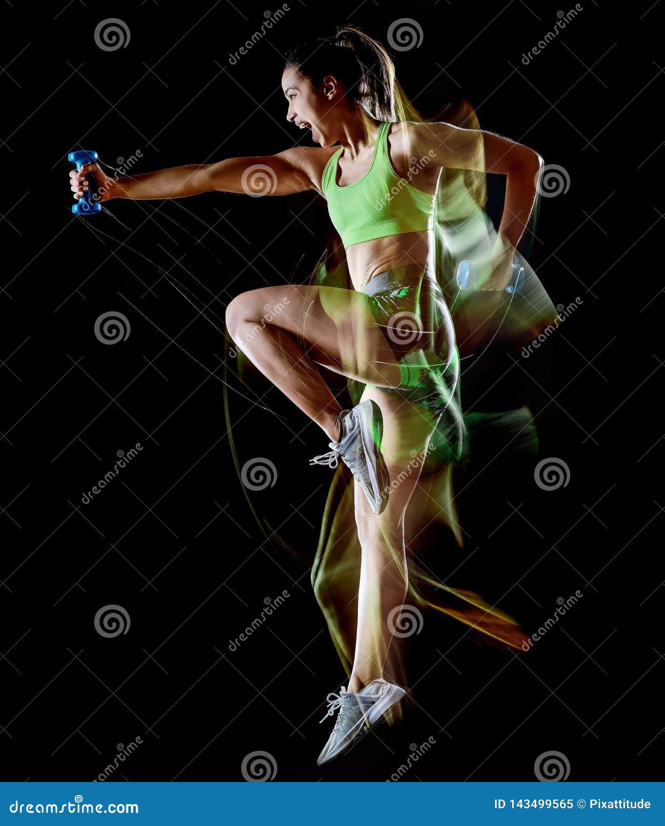 Femme exerçant l effet lightpainting de fond noir d isolement par exercices de forme physique