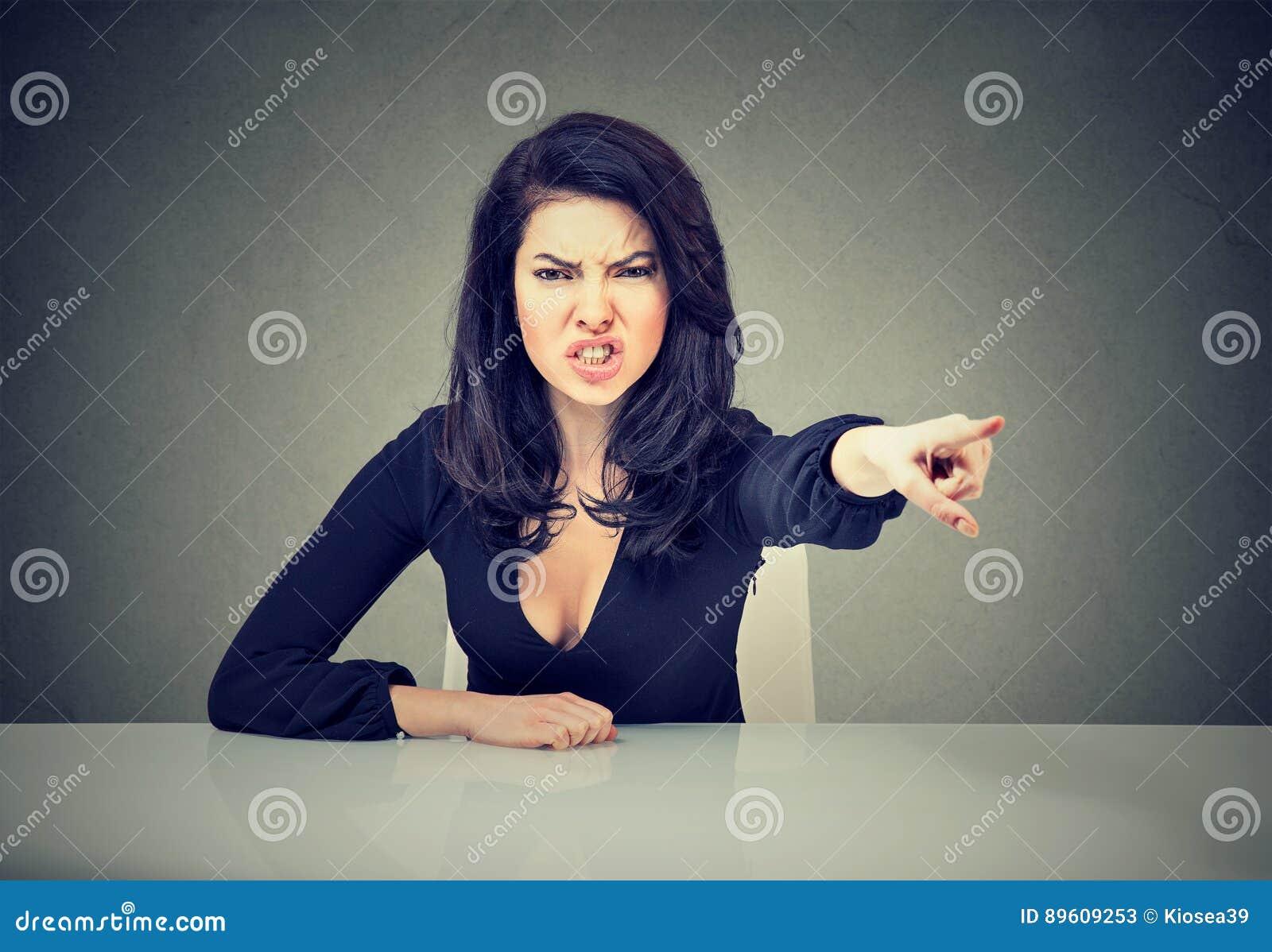 Femme fâchée d affaires s asseyant à son bureau et pointage criard avec le doigt à sortir