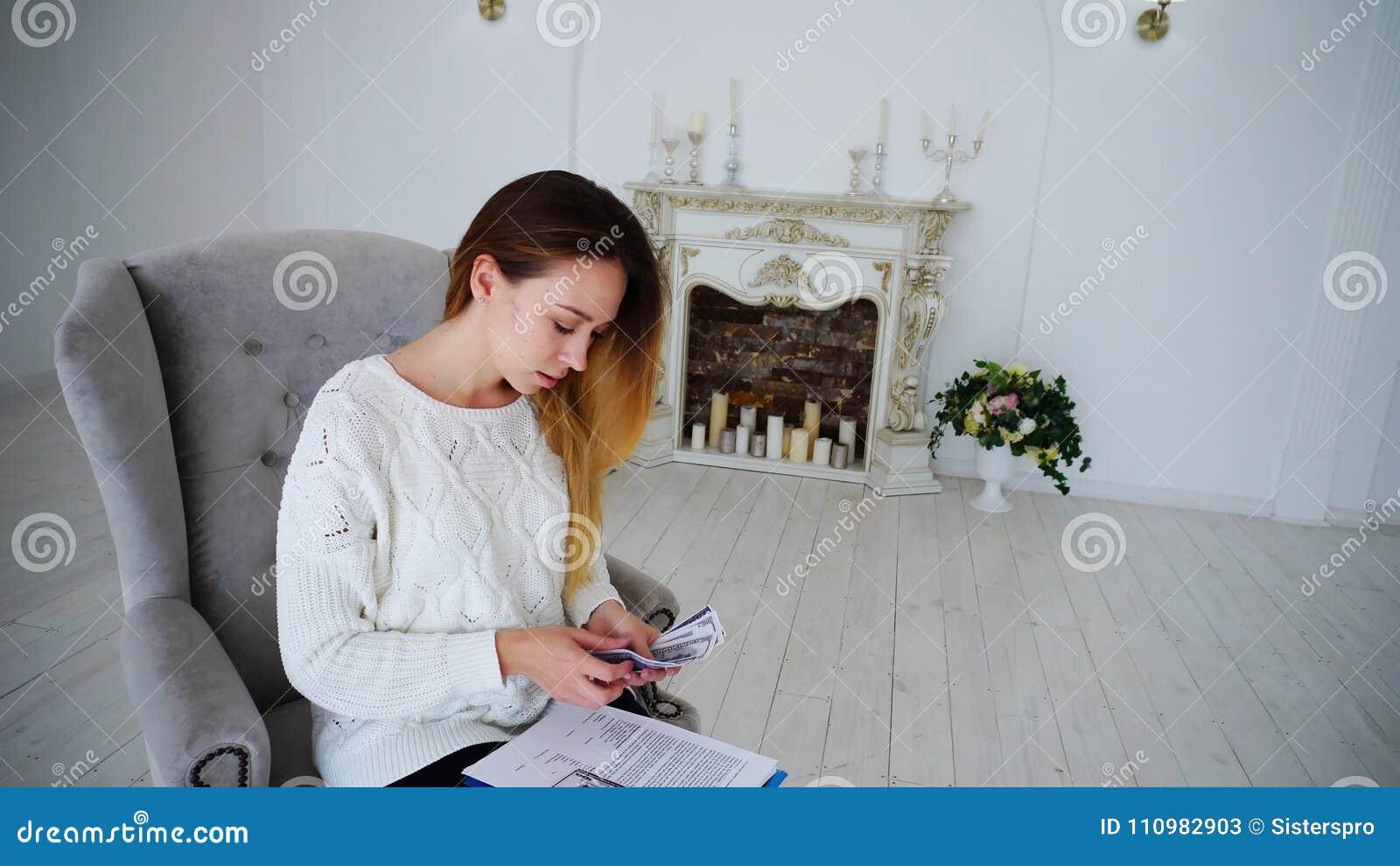 Femme féminine moderne d affaires traitant l argent et lisant la documentation de travail,