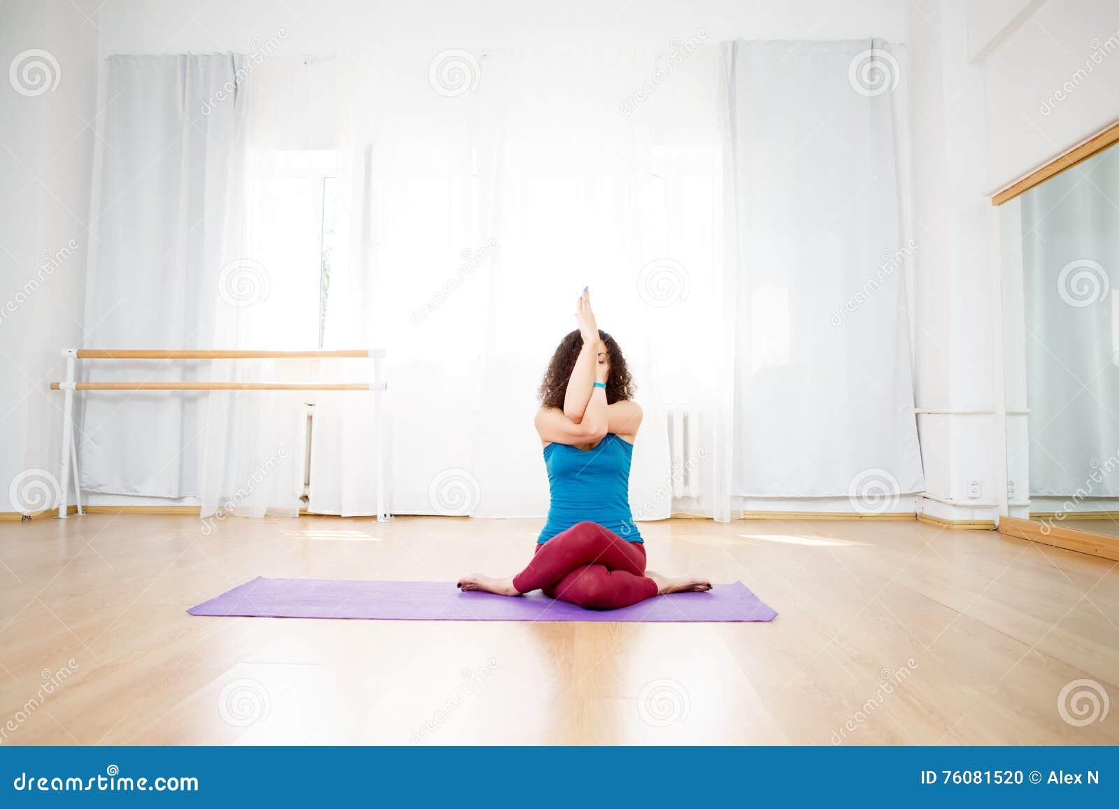 Femme faisant l exercice de yoga avec ses bras et jambes croisés