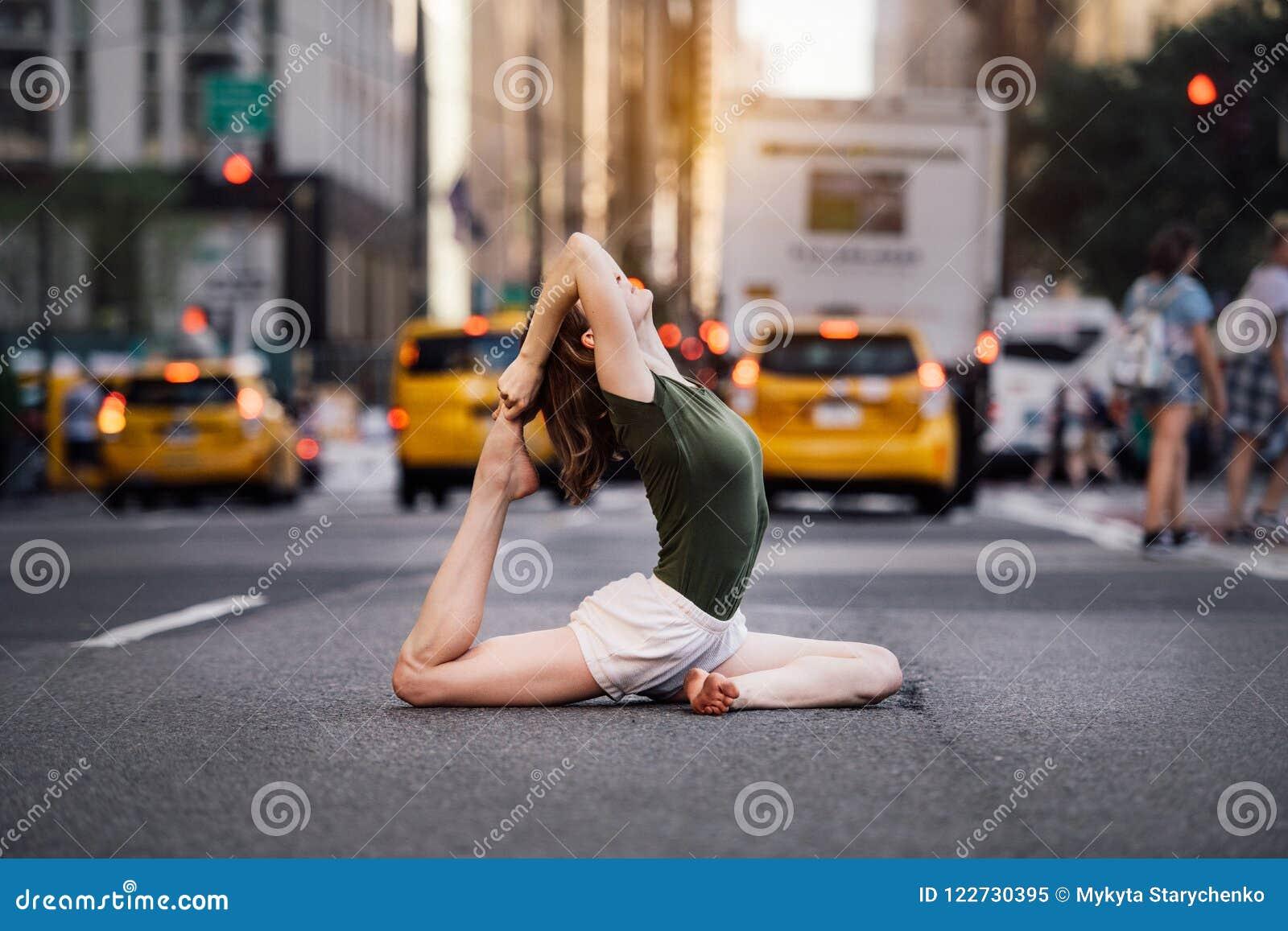 Femme faisant la pose de yoga sur la rue de ville de New York