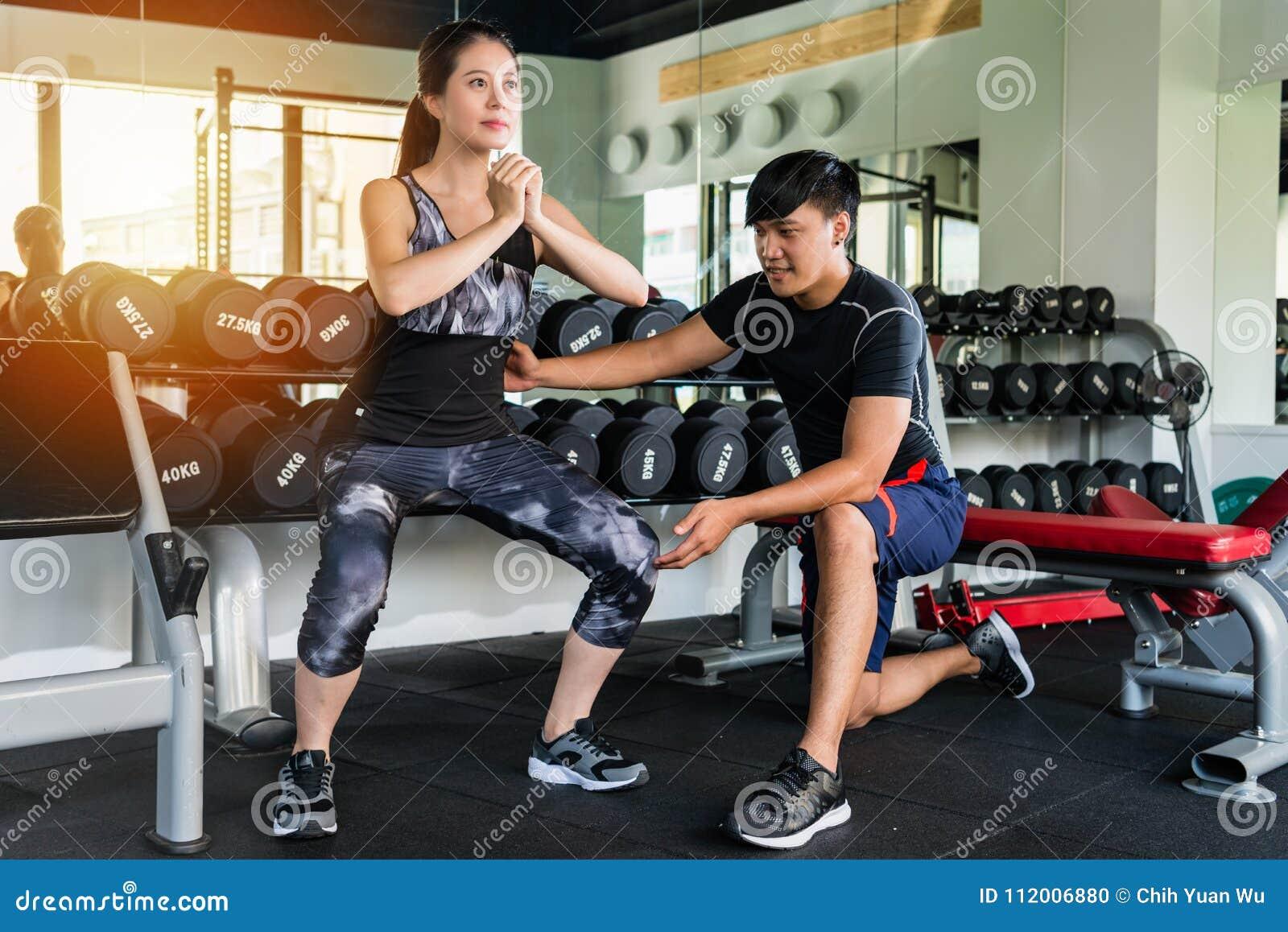 Femme faisant la posture accroupie avec un entraîneur personnel