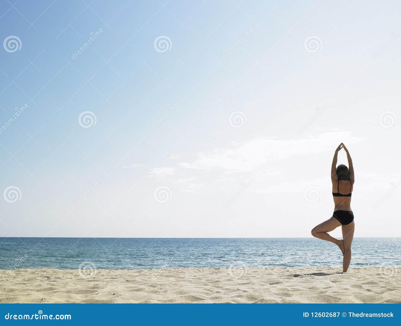 Femme faisant le yoga à la plage