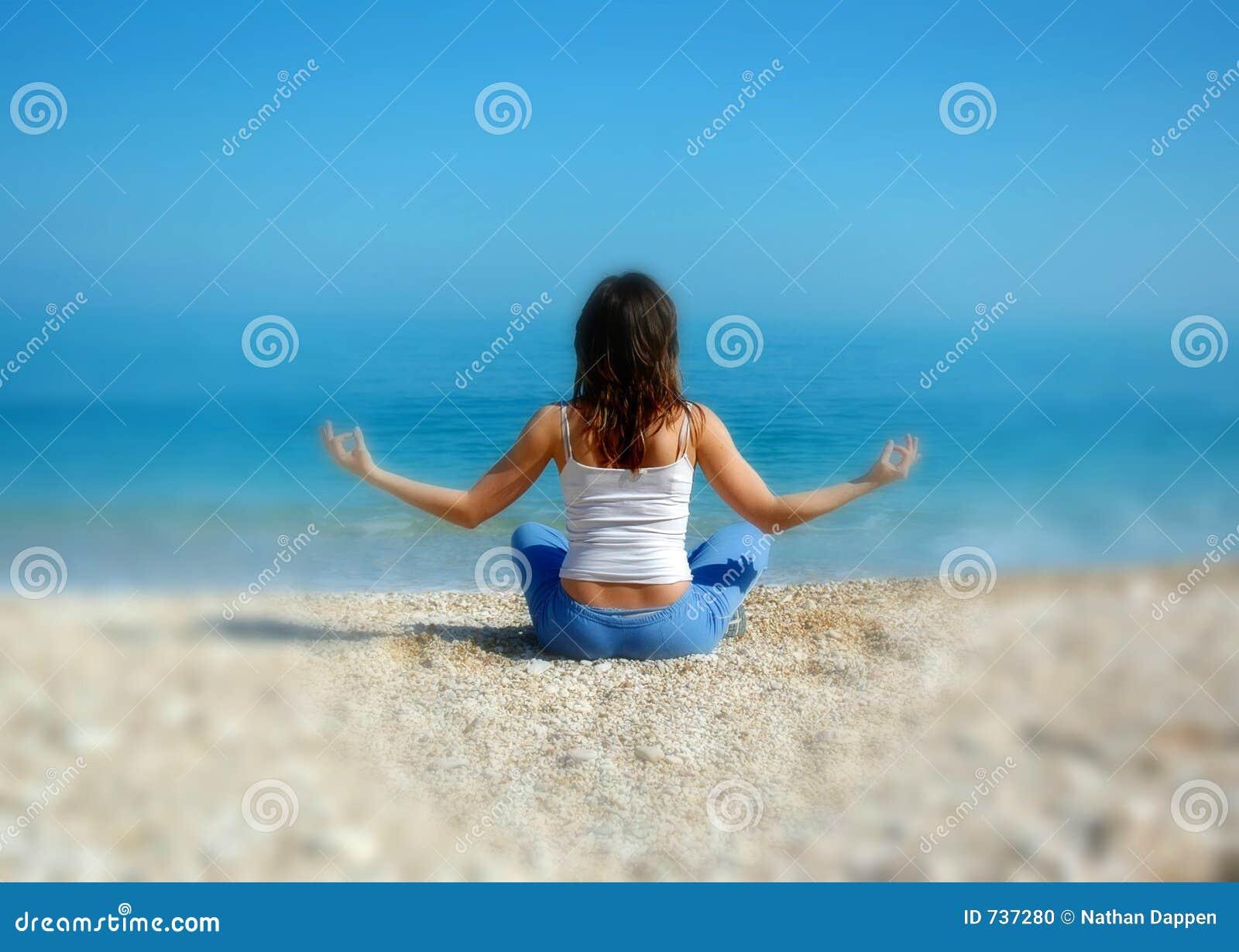 Femme faisant le yoga sur la plage