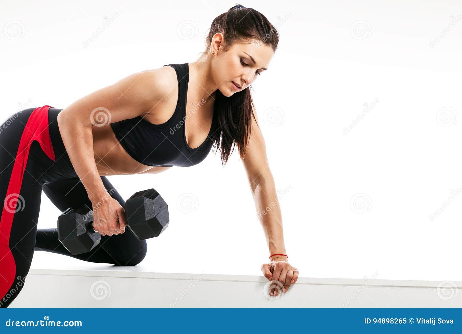 La jeune femme sportive de brune faisant un exercice avec une haltère sur  le biceps se penchant sur un banc de sports sur un blanc a isolé le fond fdae87b65af