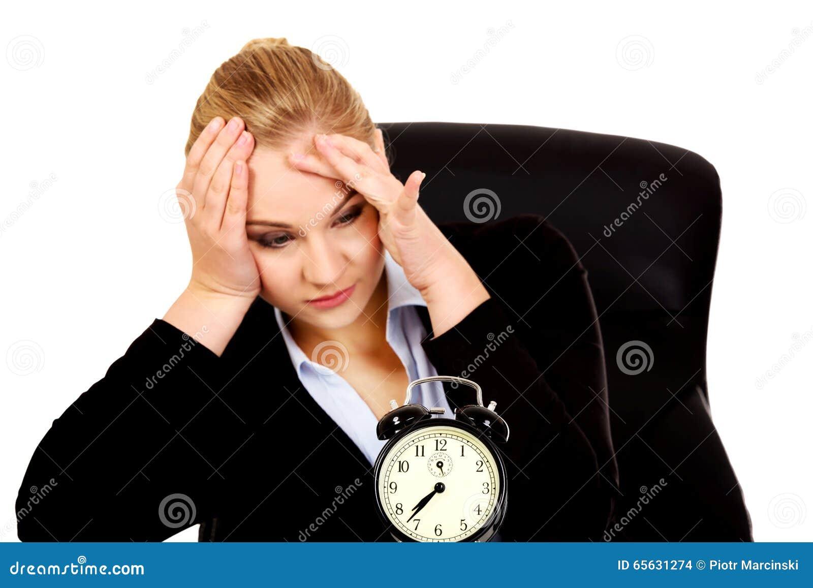 Femme fatiguée d affaires derrière le bureau avec le réveil