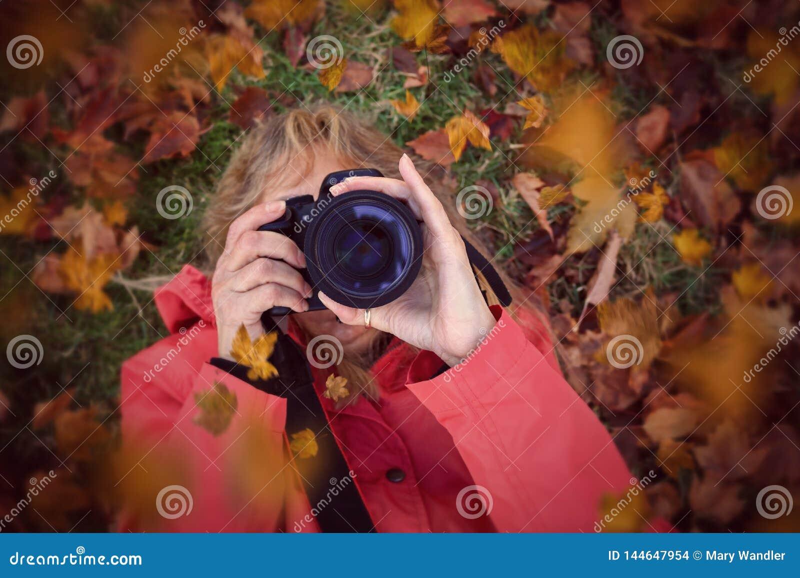 Femme focalisant une caméra s étendant dans des feuilles d automne