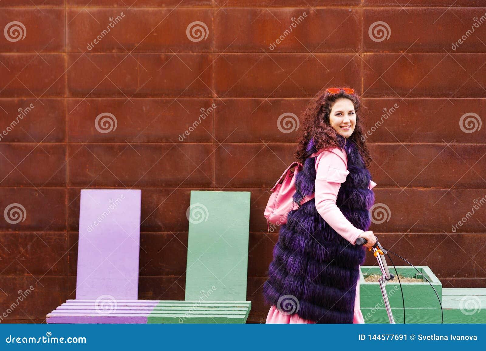 Femme gaie dans une robe rose et un cap pourpre de fourrure montant un scooter
