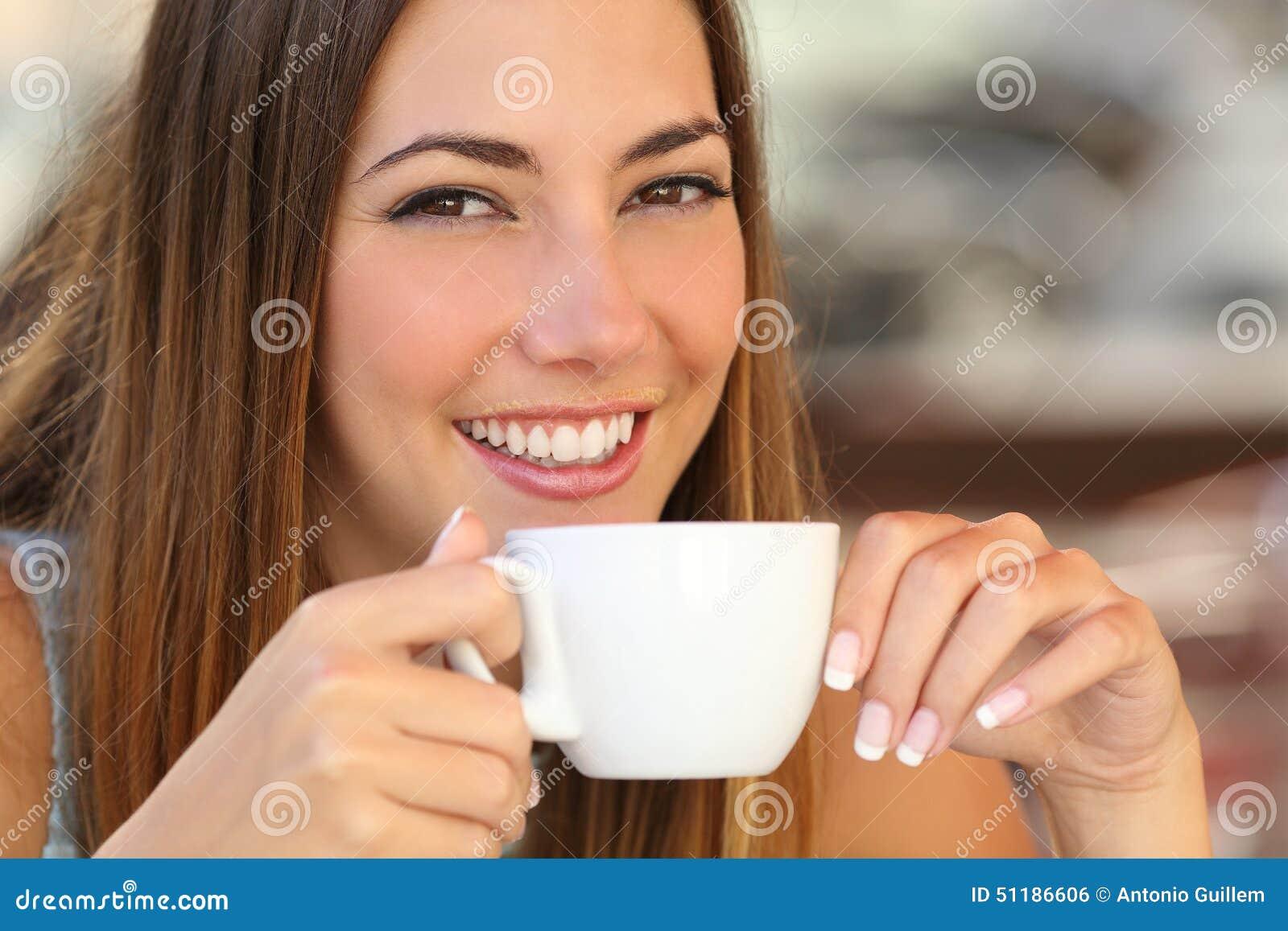 Femme goûtant un café d une tasse dans une terrasse de restaurant