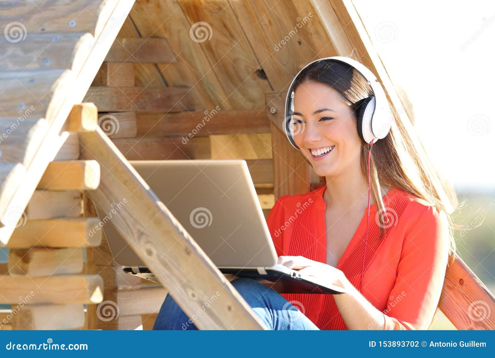 Femme heureuse à l aide de l ordinateur portable et des écouteurs dans une maison en bois