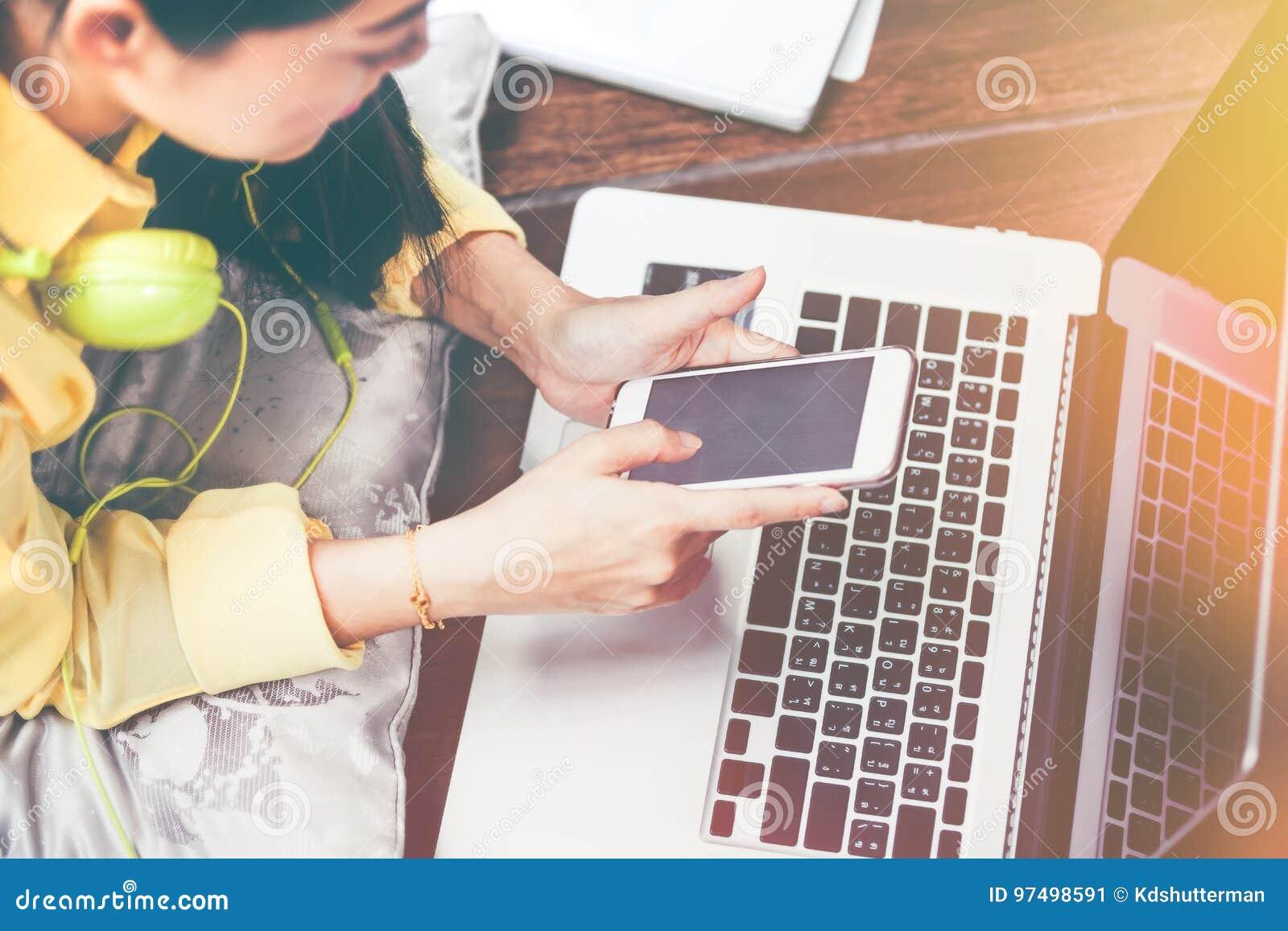 Femme heureuse à l aide du téléphone et de l ordinateur portable intelligents Effet de vintage