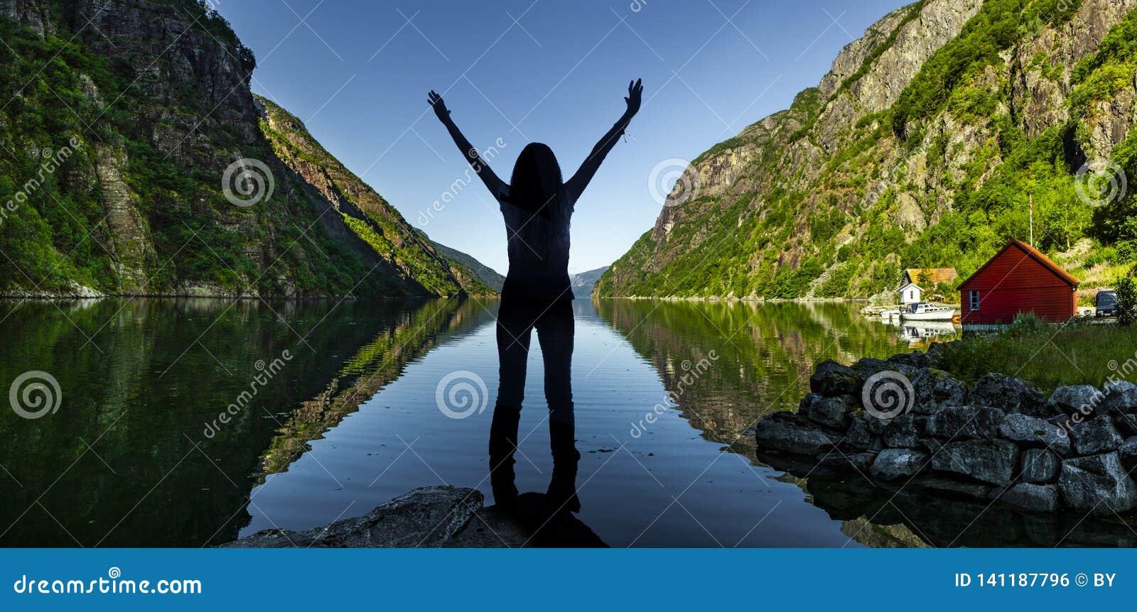 Femme heureuse à un fjord en Norvège