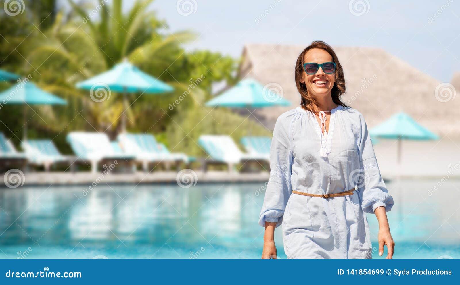 Femme heureuse au-dessus de piscine de station de vacances touristique