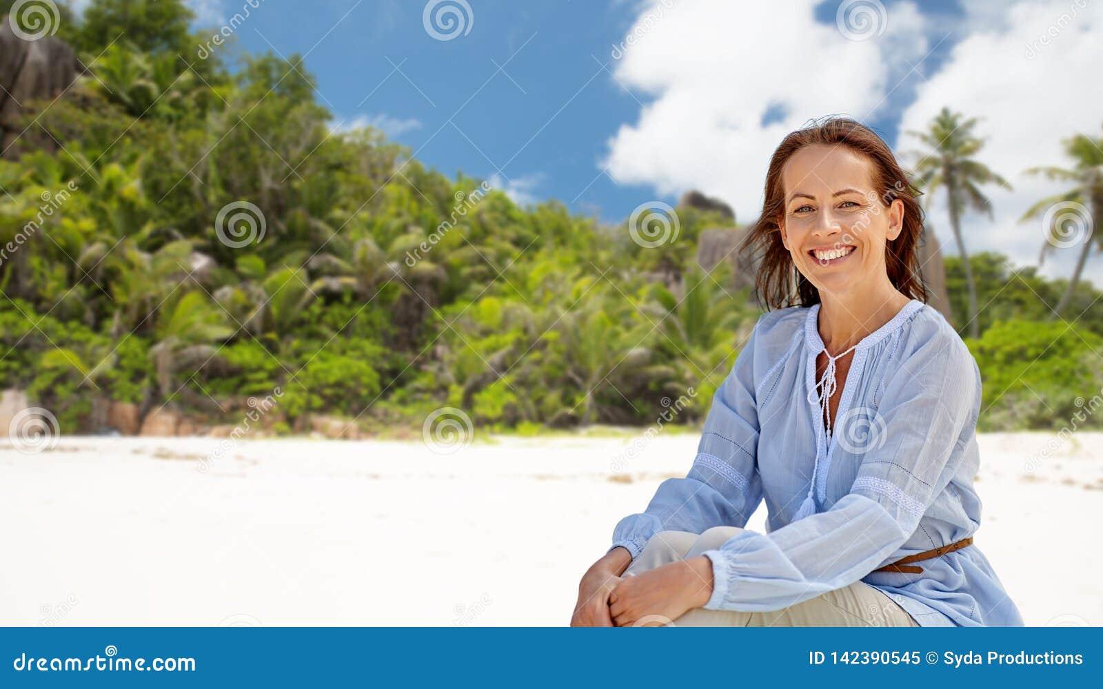 Femme heureuse au-dessus de plage tropicale d île des Seychelles
