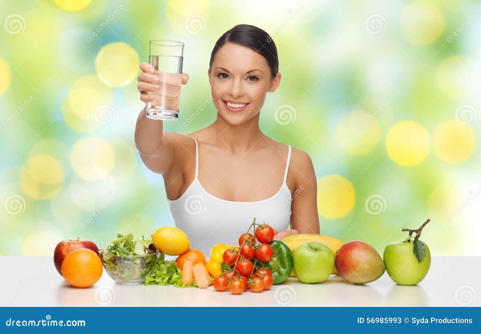 Femme heureuse avec la nourriture saine montrant le verre d eau