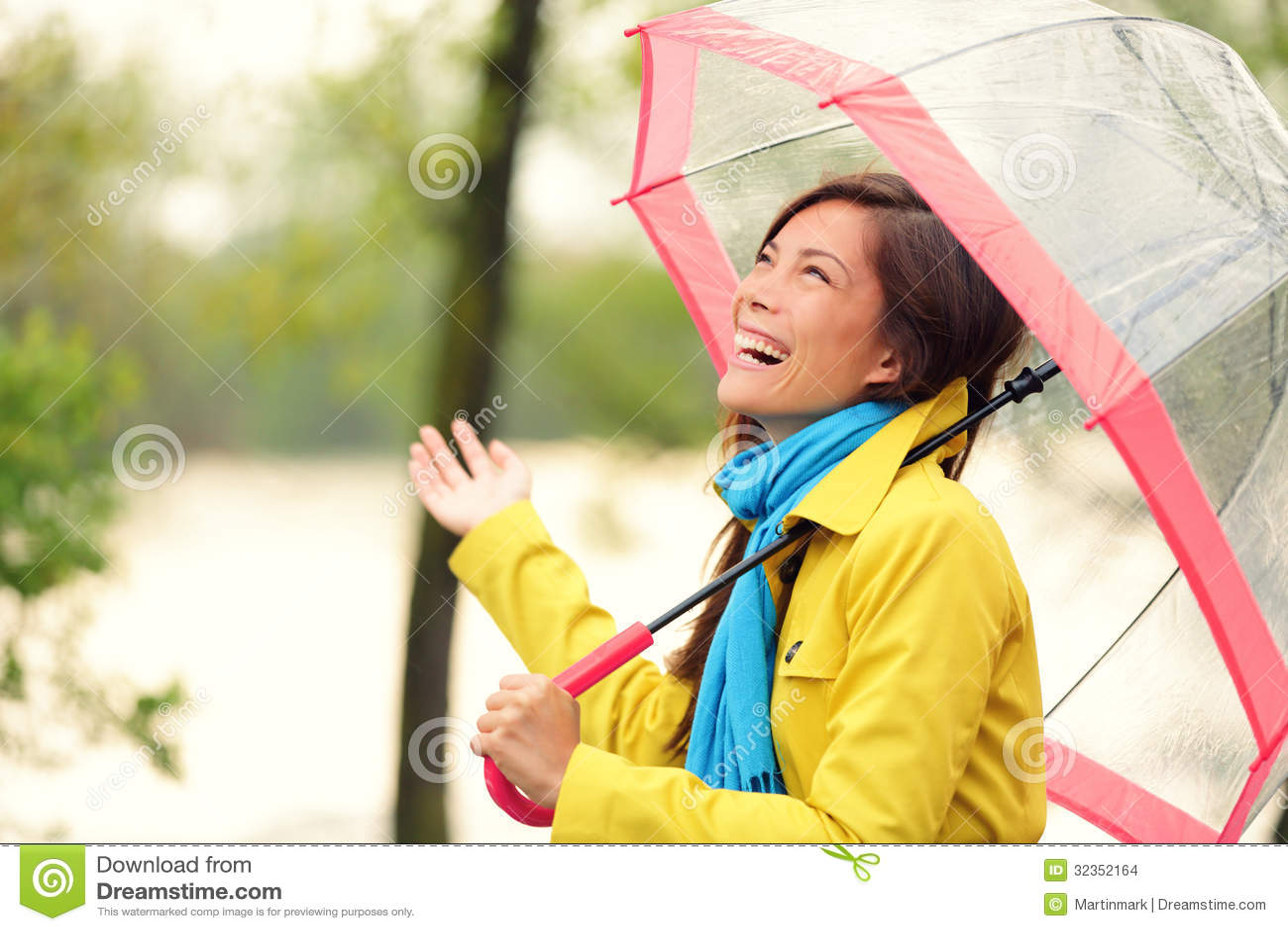 Femme heureuse avec le parapluie sous la pluie