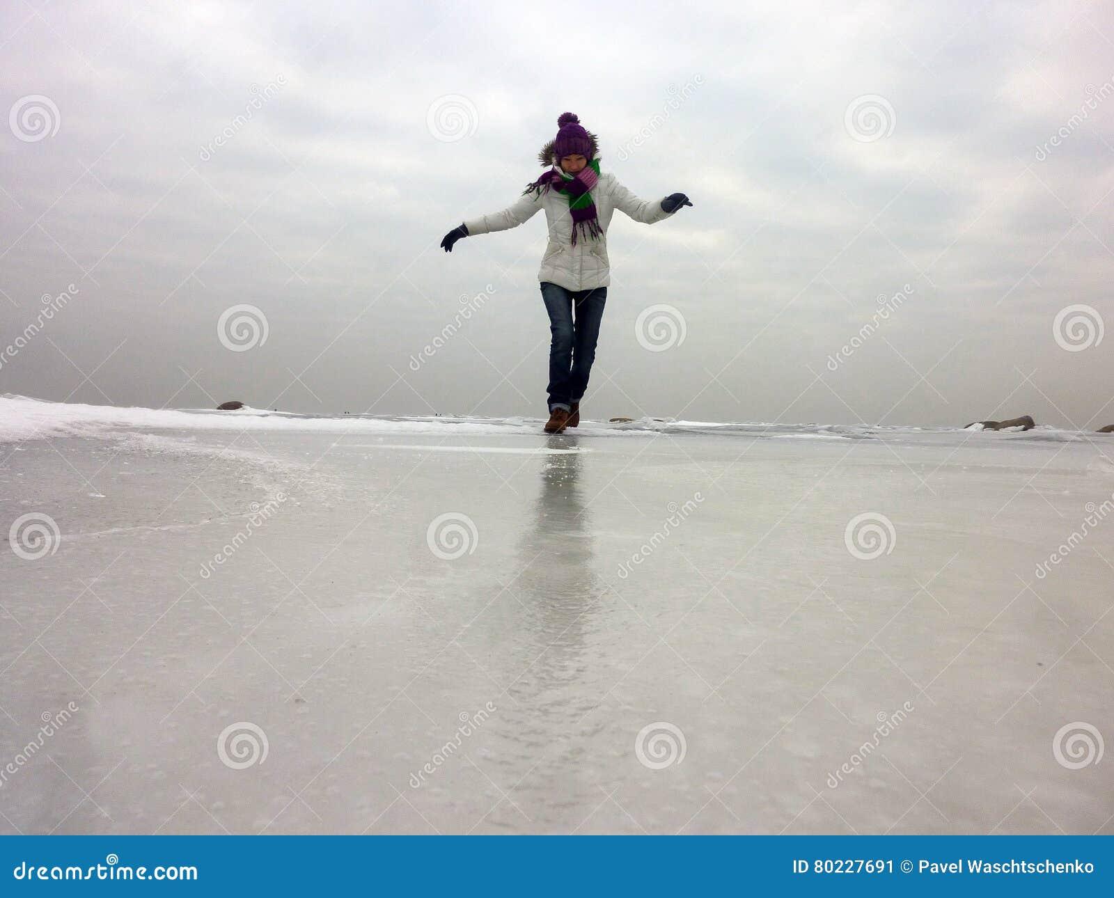 Femme heureuse courant sur la mer congelée par jour froid