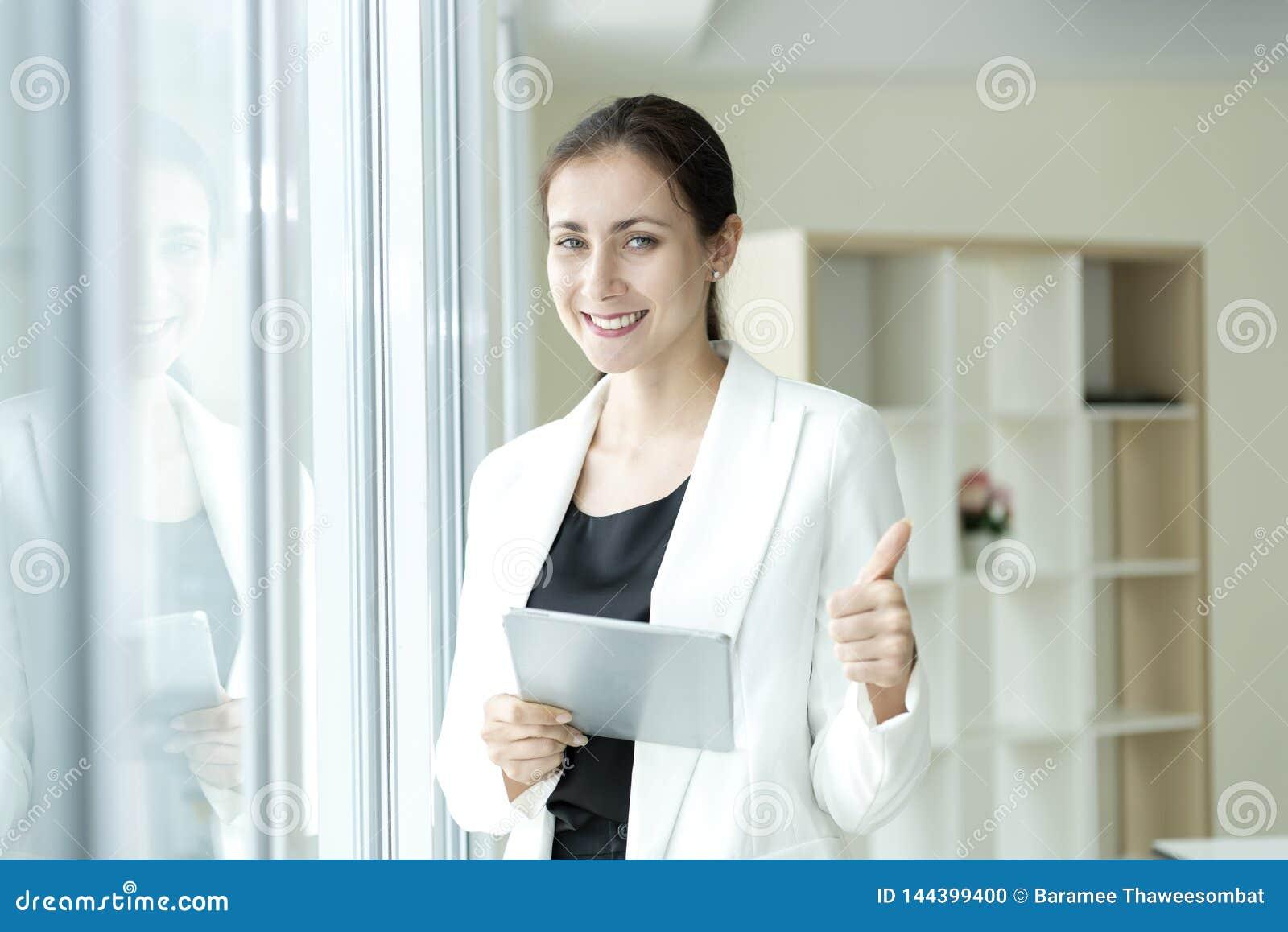 Femme heureuse d affaires regardant la cam?ra avec le pouce de position  Concept r?ussi