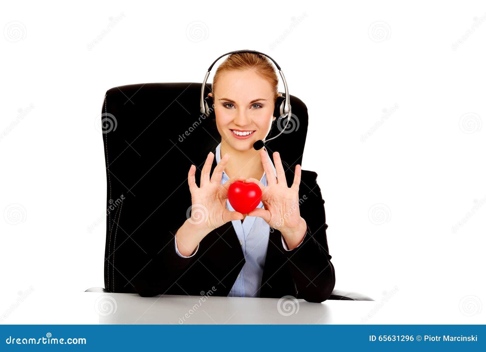 Femme heureuse d opérateur de téléphone tenant le jouet de coeur