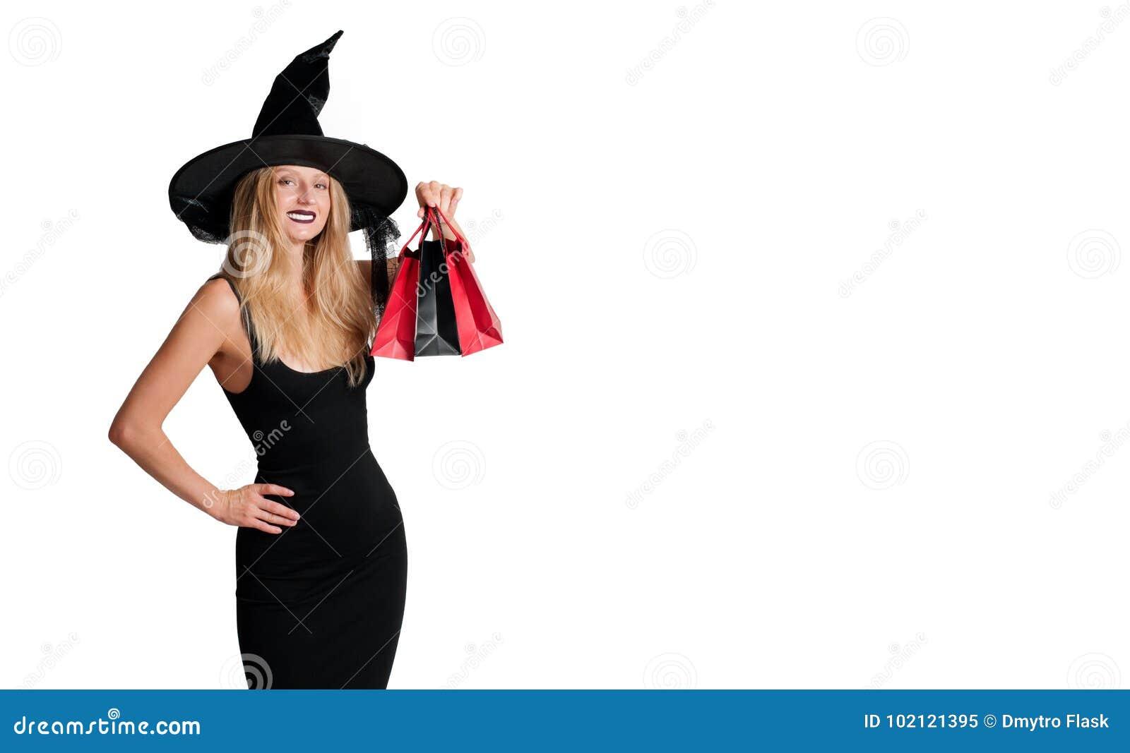 Femme heureuse dans le costume de Halloween de sorcière avec le chapeau