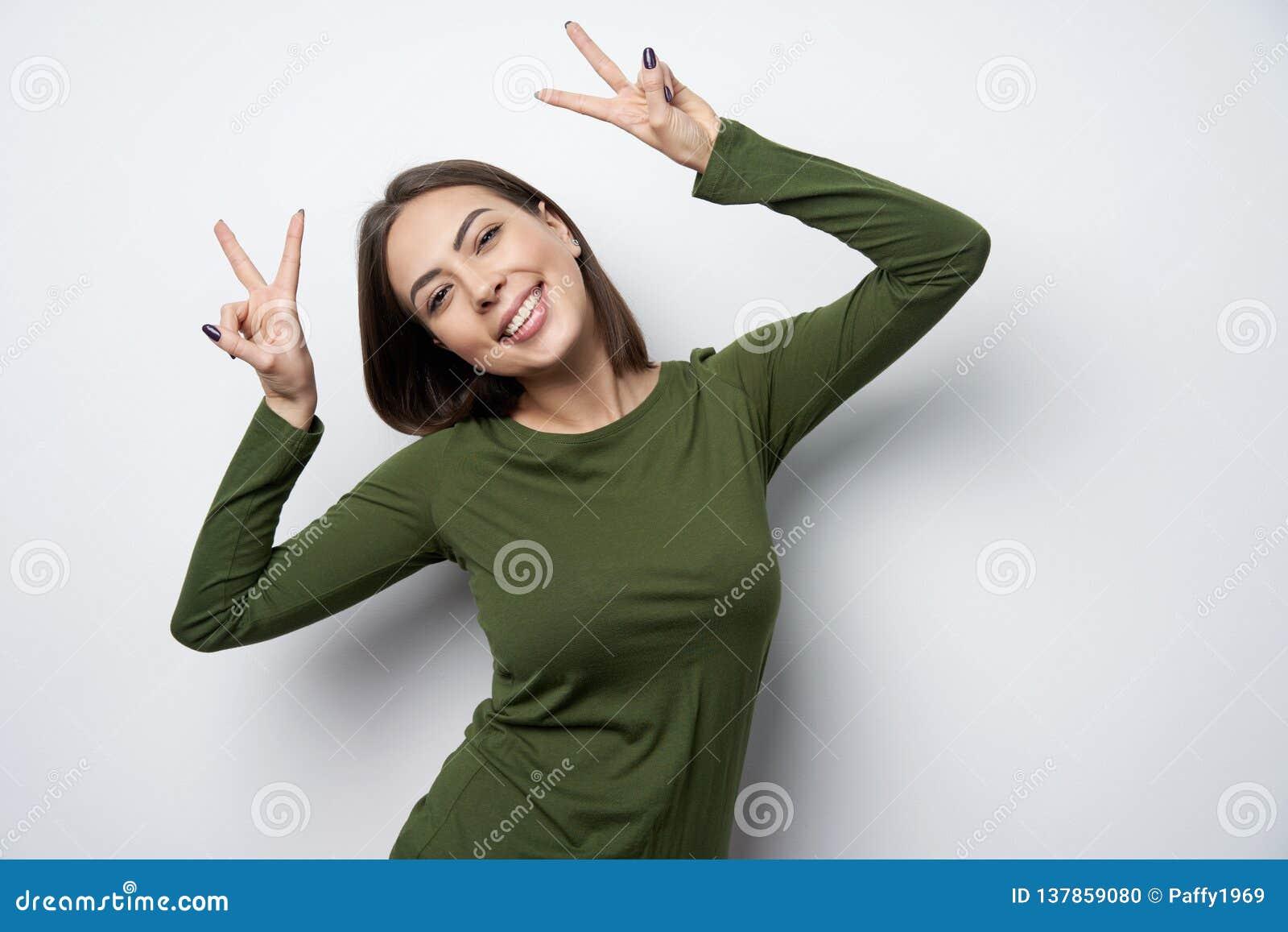 Femme heureuse de brune faisant des gestes le sourire de signe de paix