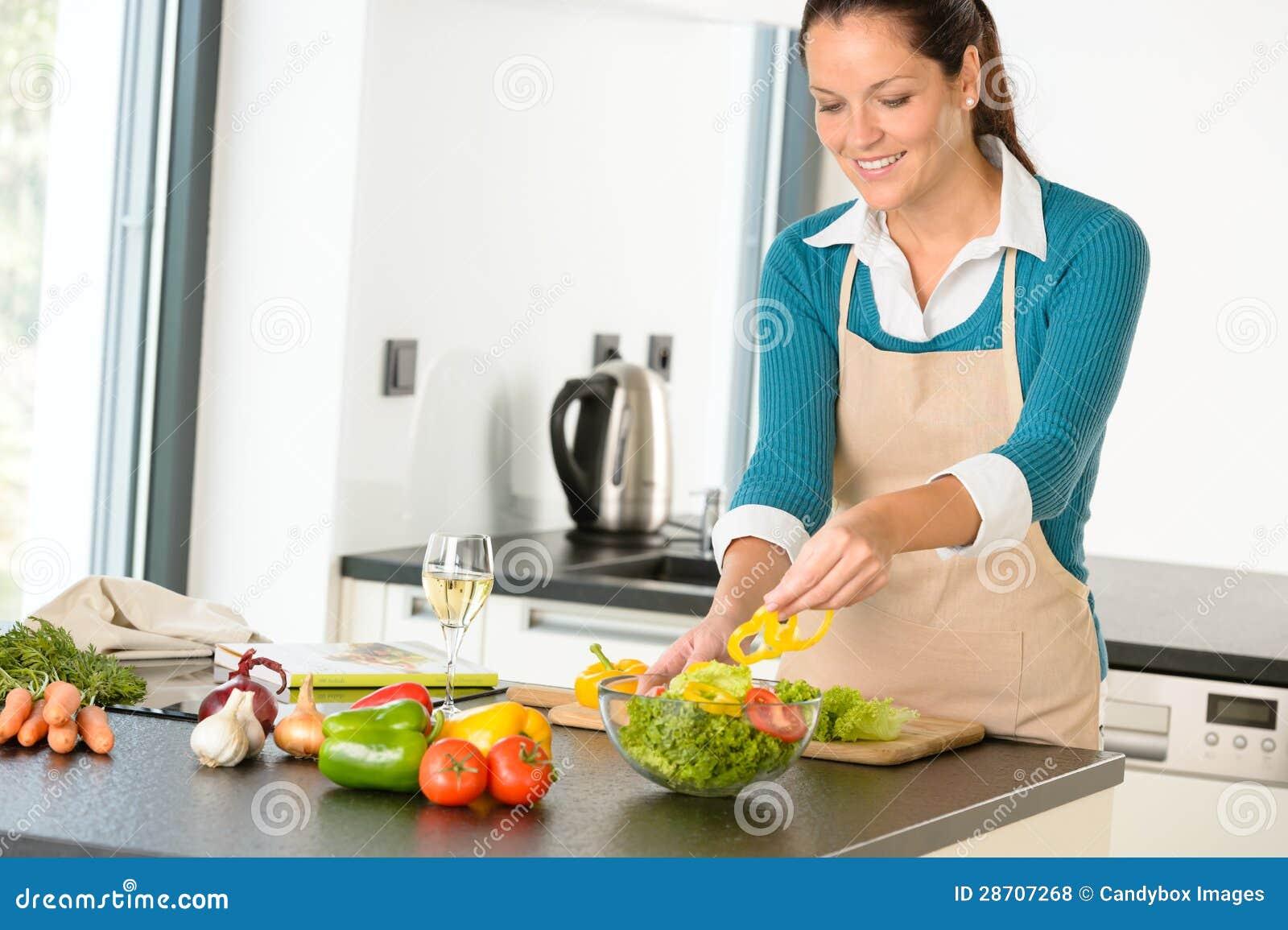 Femme heureuse effectuant à légumes de cuisine de salade la cuisson