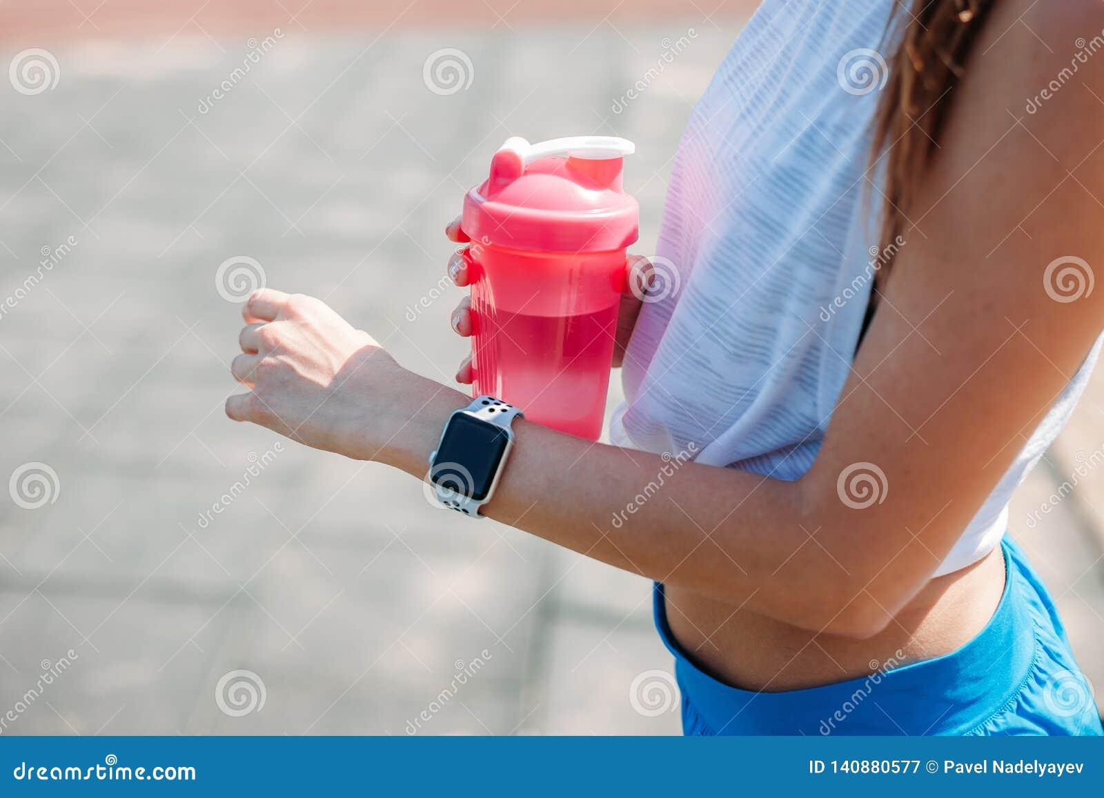 Femme heureuse employant le smartwatch pour des résultats de contrôles dans l appli de forme physique Bras de port de bracelet de