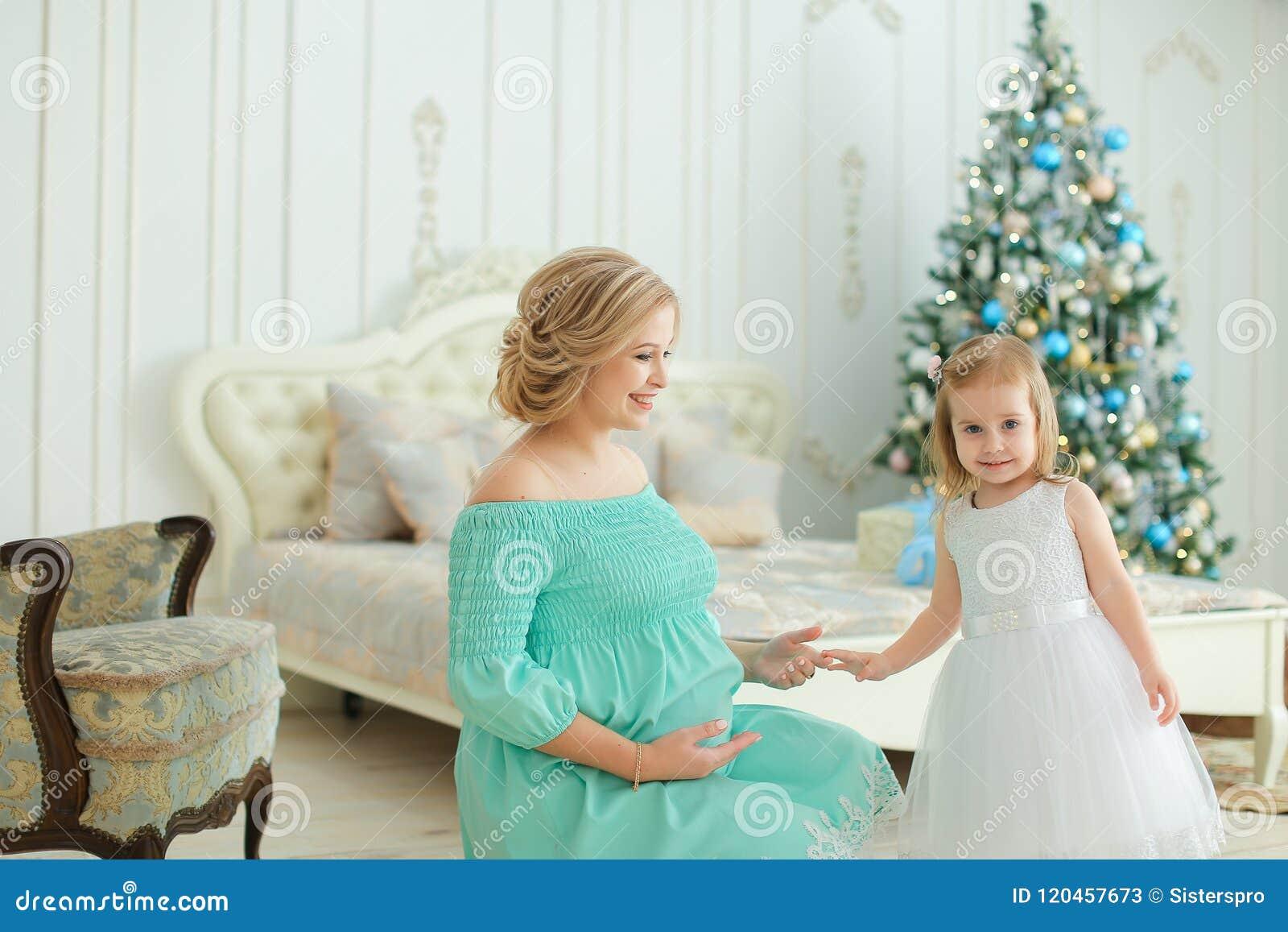 Femme heureuse enceinte portant la robe bleue étreignant le ventre et se reposant avec la petite fille près de l arbre de Noël da