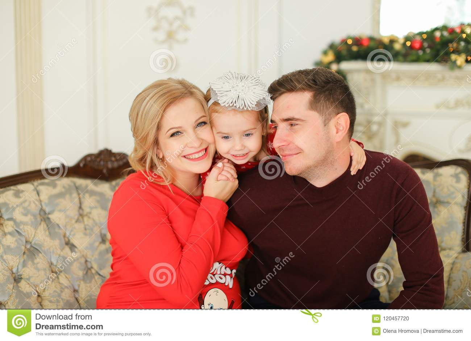 Femme heureuse et homme s asseyant avec la cheminée décorée proche de petite fille