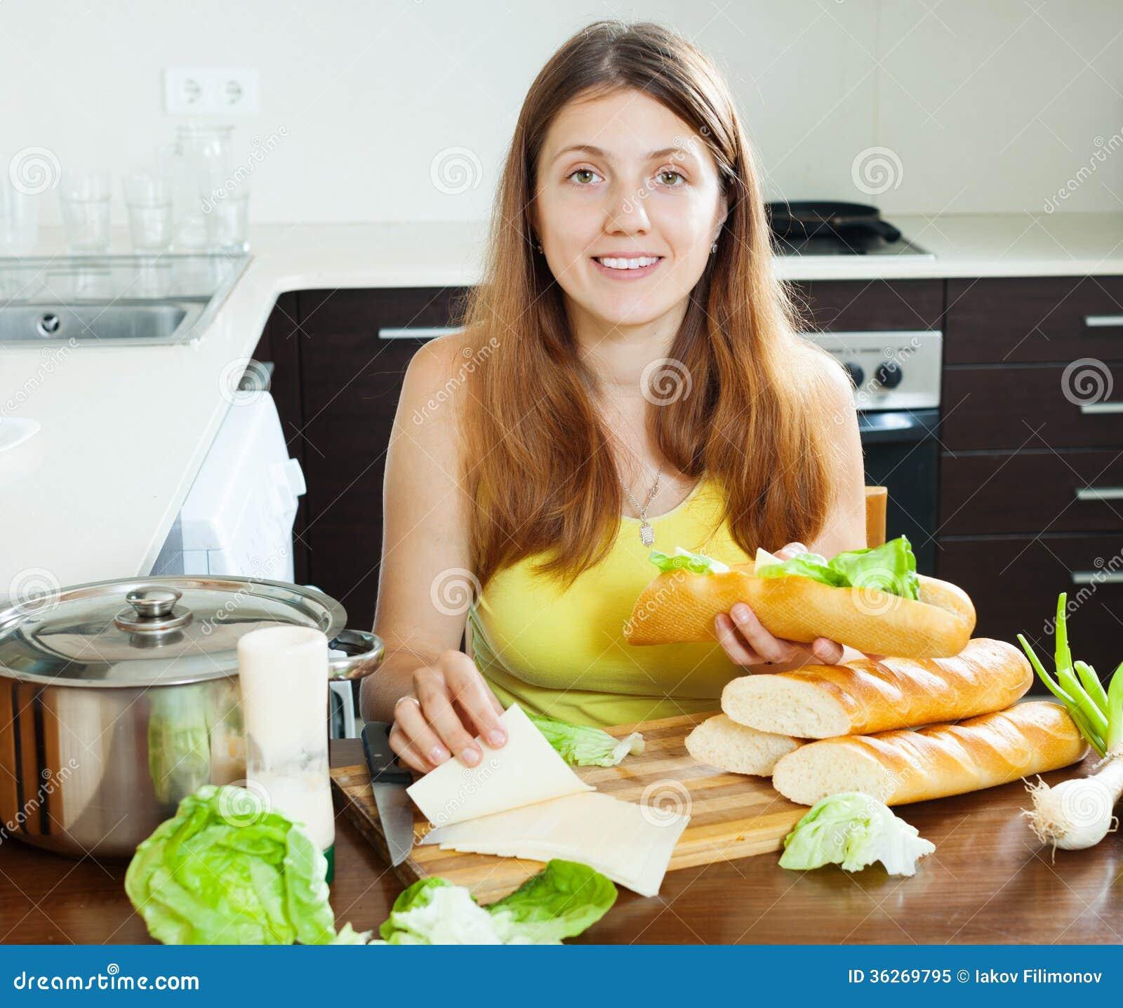 Femme heureuse faisant cuire des sandwichs avec du fromage