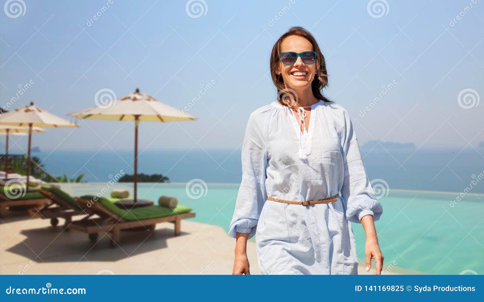 Femme heureuse marchant au-dessus de la piscine de bord d infini