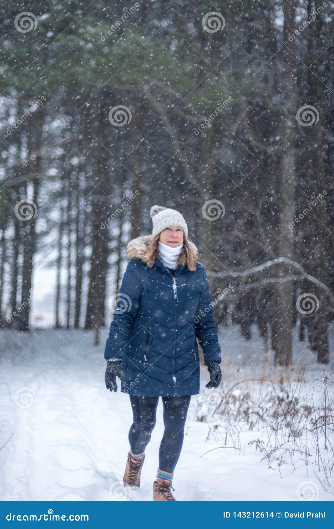 Femme heureuse marchant en bois d hiver regardant la chute de neige