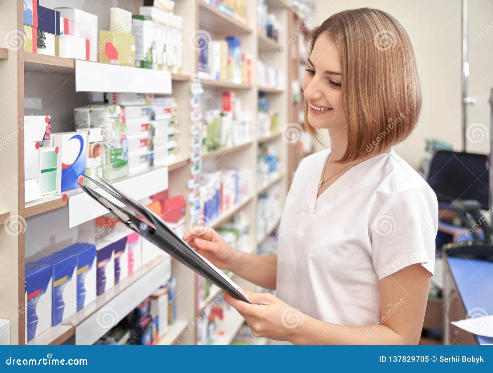Femme heureuse posant tout en travaillant dans la pharmacie